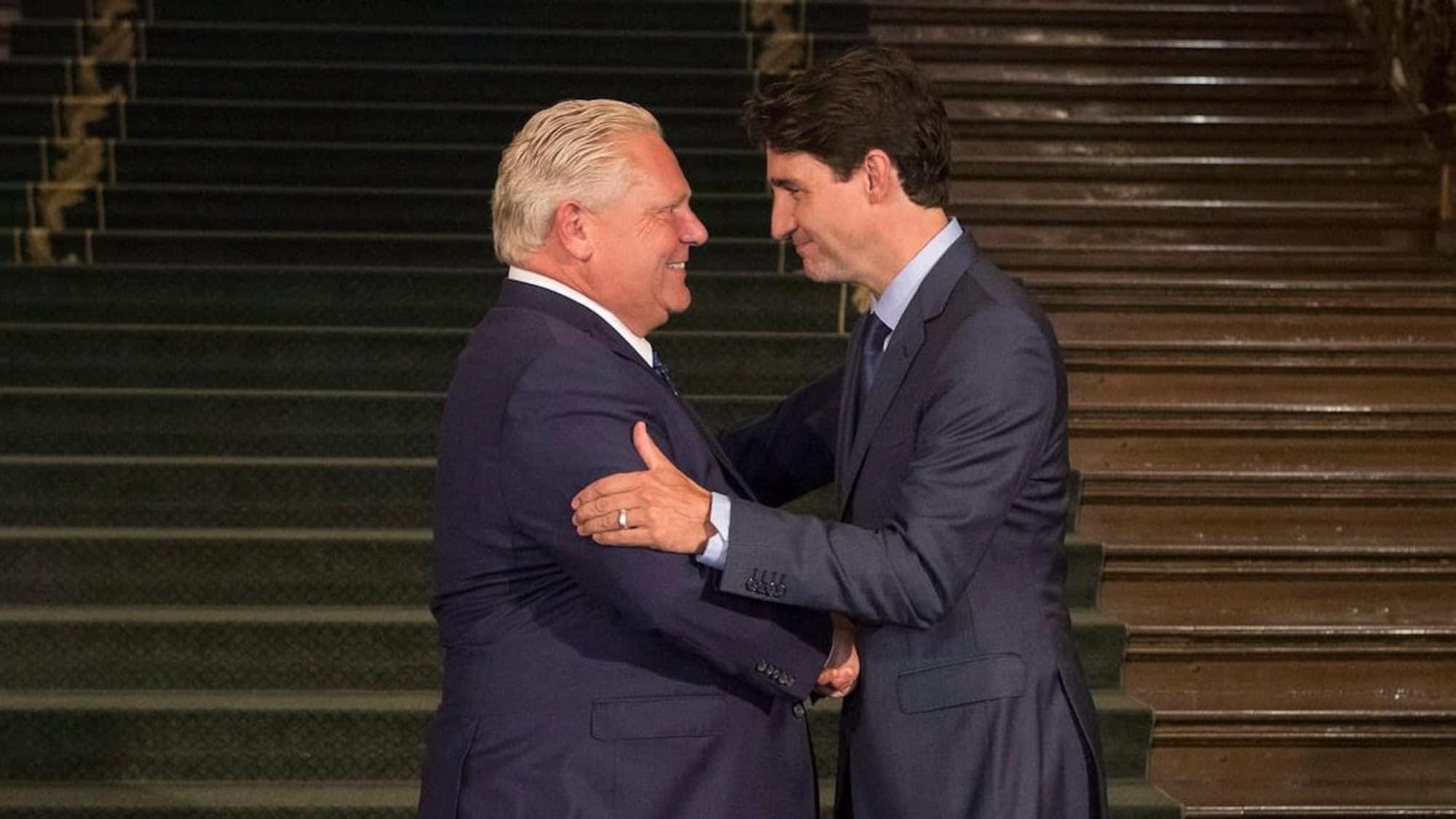 Doug Ford et Justin Trudeau se serre la main.