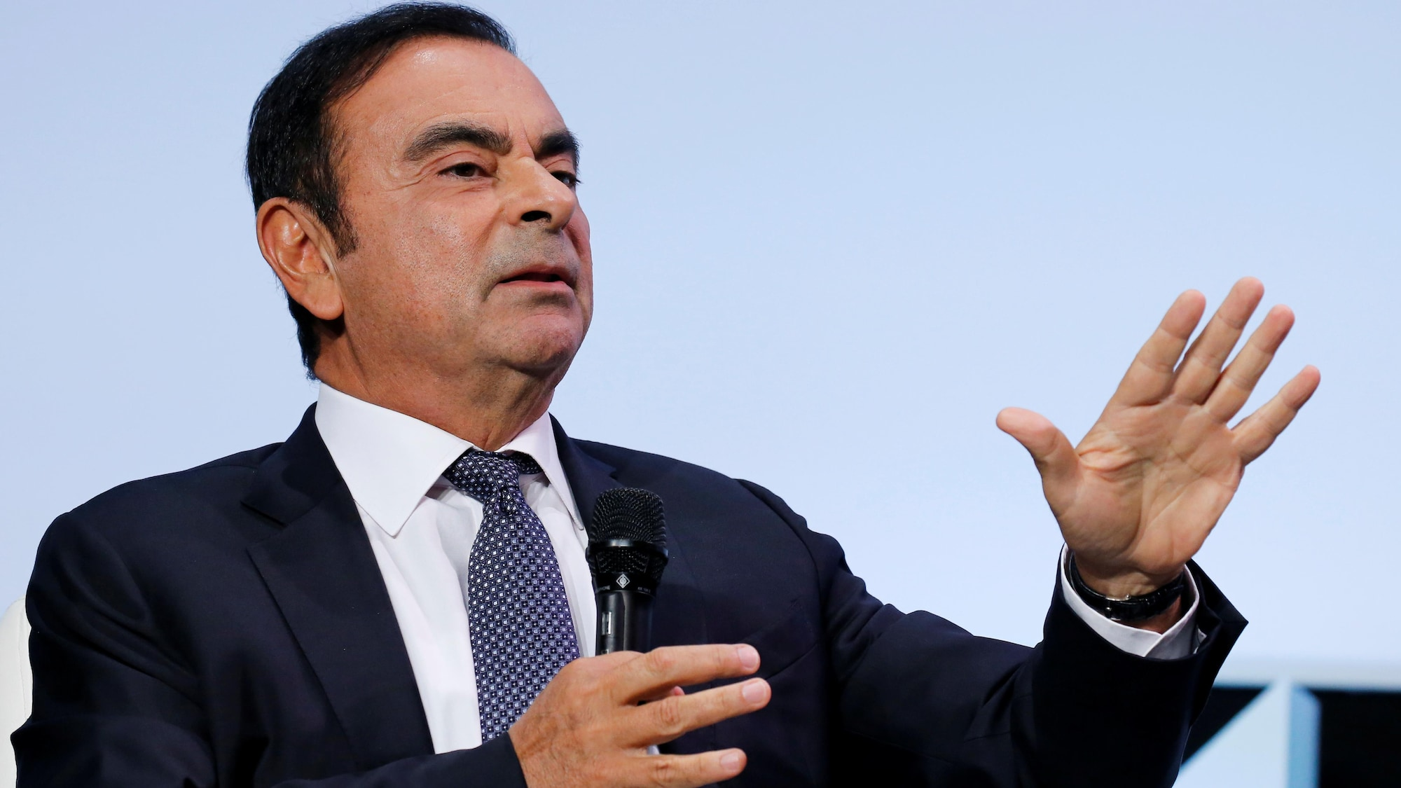 Carlos Ghosn tient un micro.