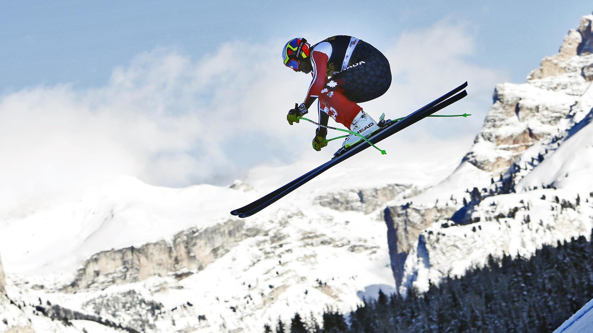 Manuel Osborne-Paradis effectue un saut avec, en arrière-plan, des montagnes.