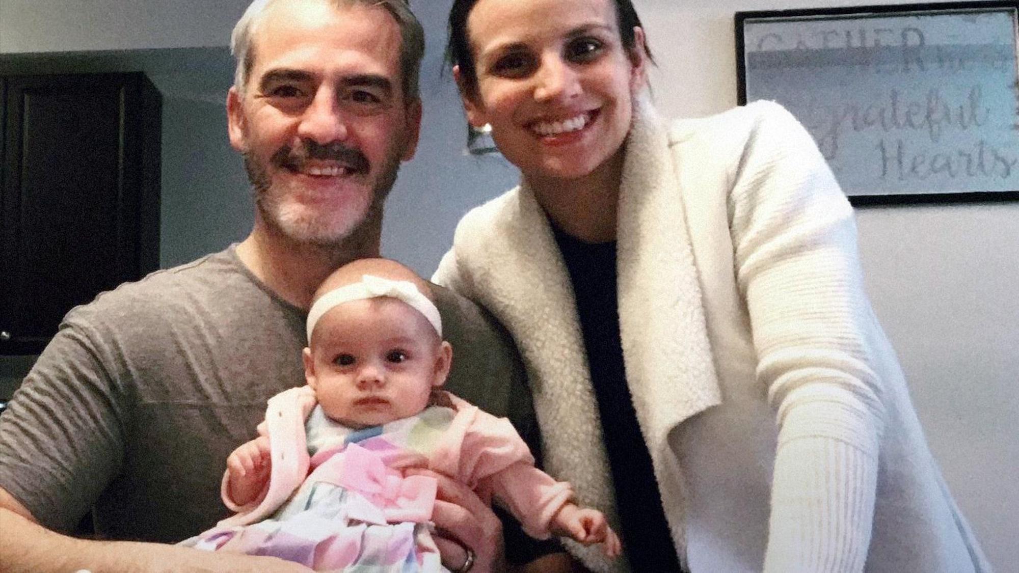 Bruno Marcotte et Meagan Duhamel regardent la caméra en tenant leur fille Zoey, qui est assise sur une table.