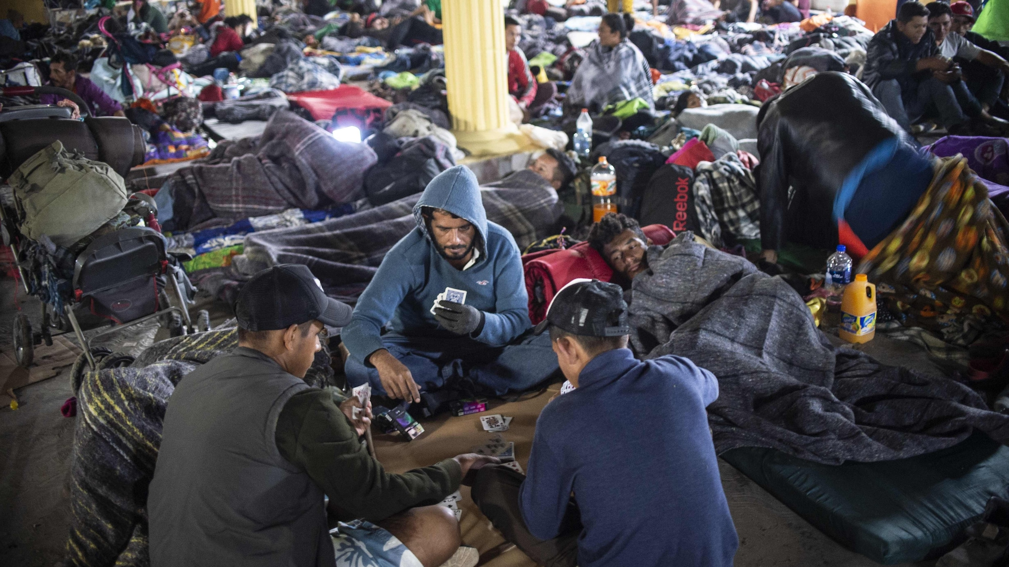 Des migrants dorment ou jouent aux cartes dans un refuge.