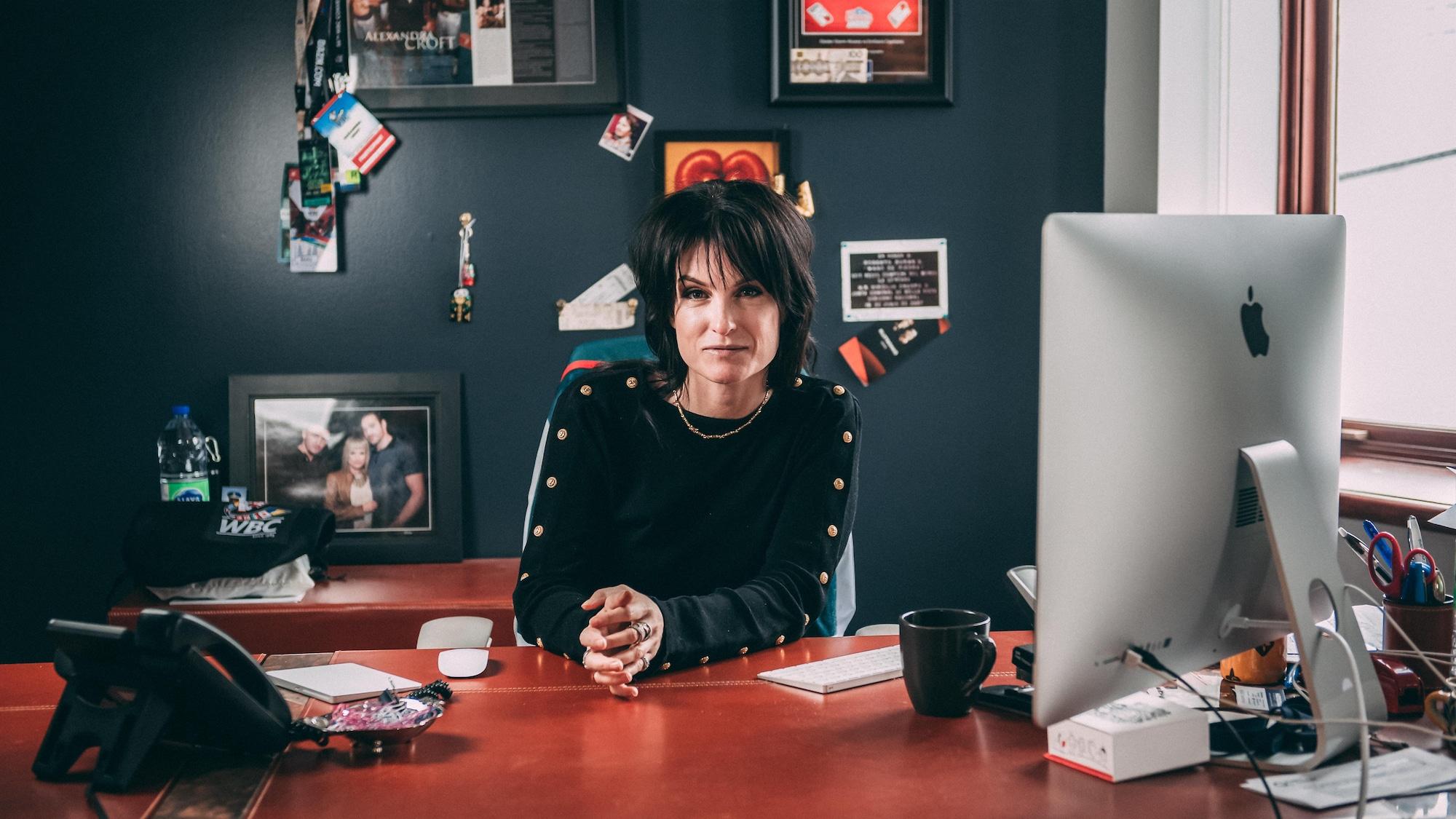 Alexandra Croft est assise à son bureau de travail.