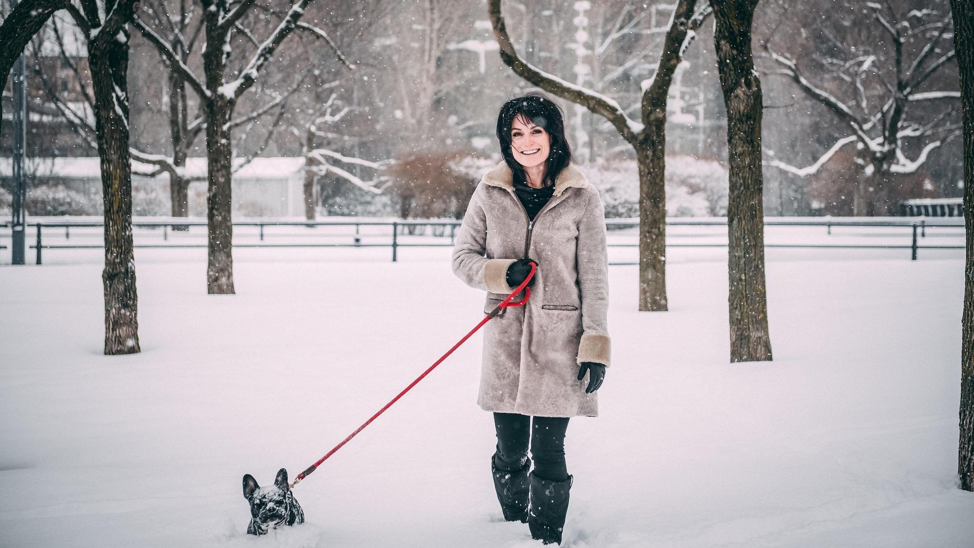 Alexandra Croft marche dans la neige avec son chien.
