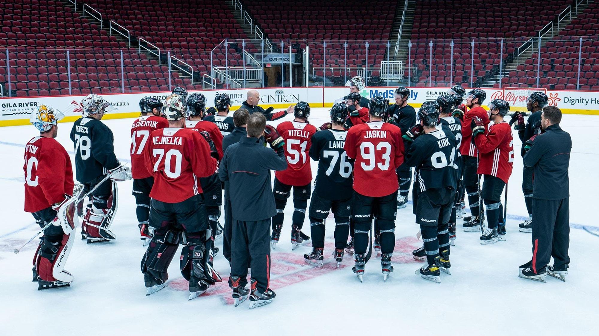 Entouré d'une vingtaine de joueurs de hockey, un entraîneur parle.