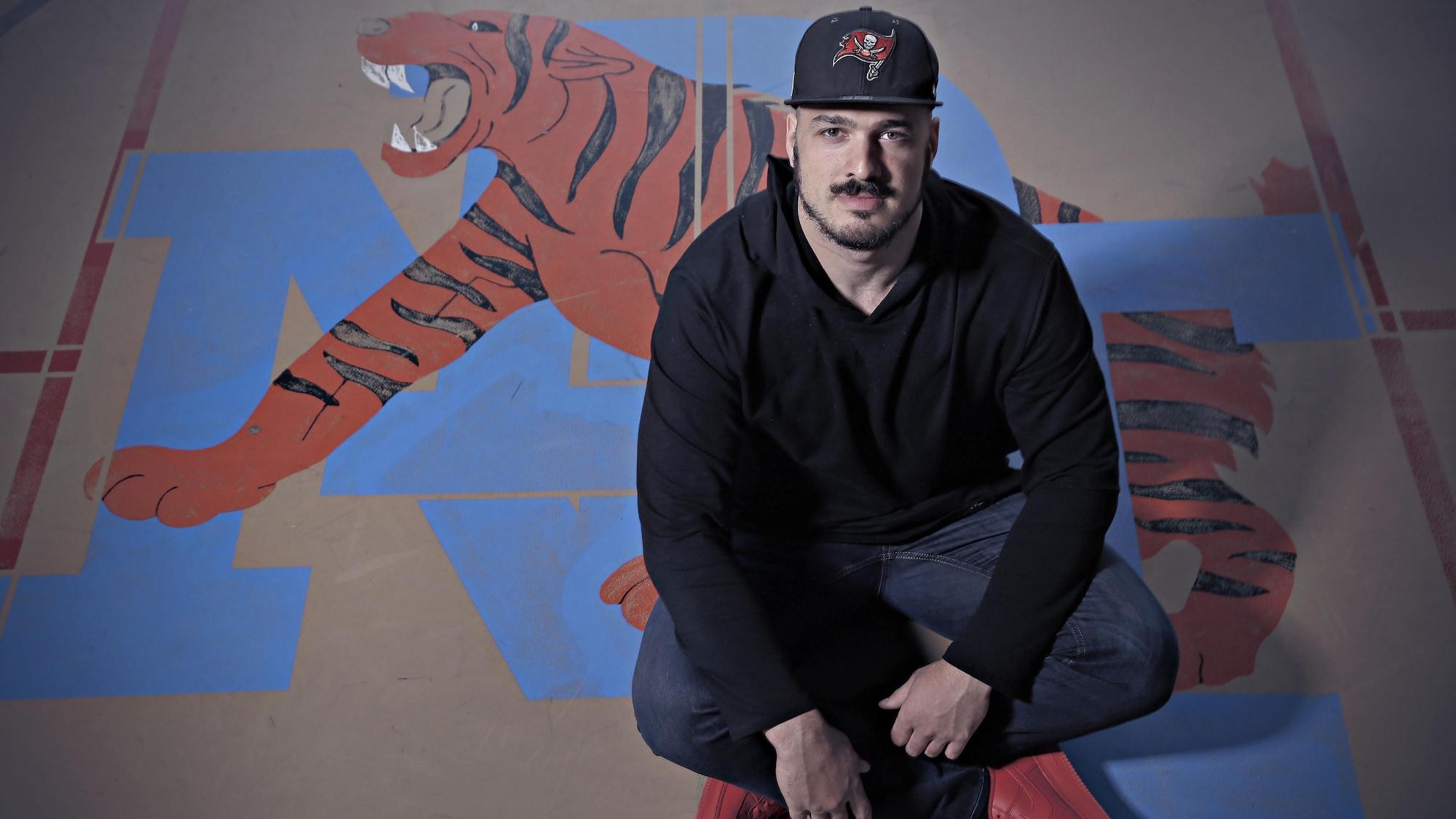 Antony Auclair est assis dans le gymnase, près du logo de son ancienne organisation sportive.