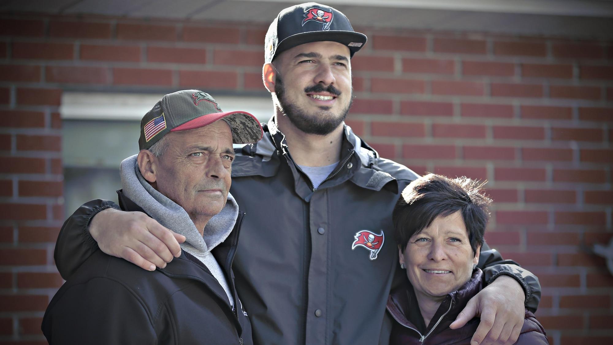 Antony Auclair a un bras autour de chacun de ses deux parents.