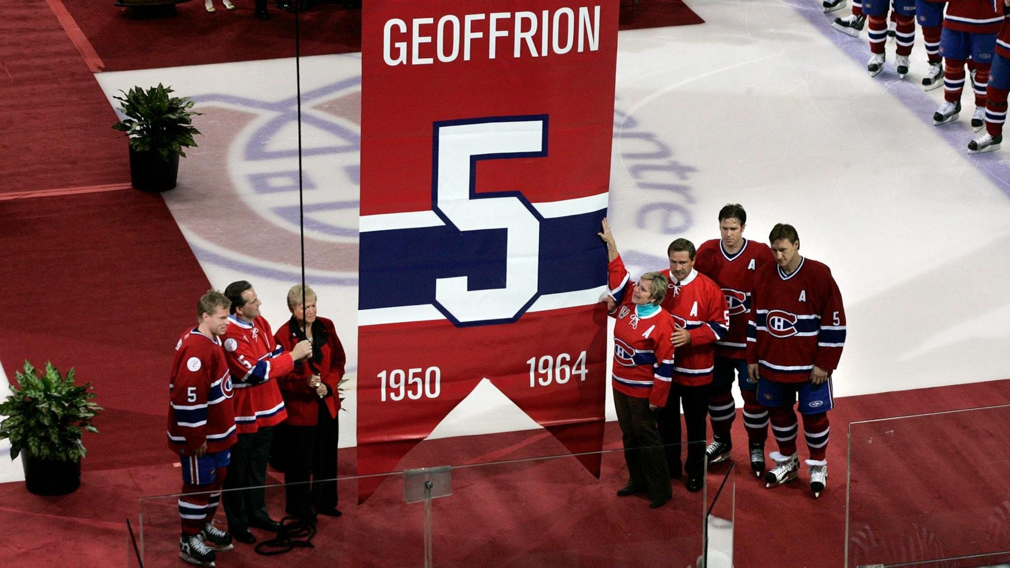 Membres de la famille et joueurs du Canadien se tiennent de chaque côté de la bannière num.ro 5 avant qu'elle soit hissée au plafond.