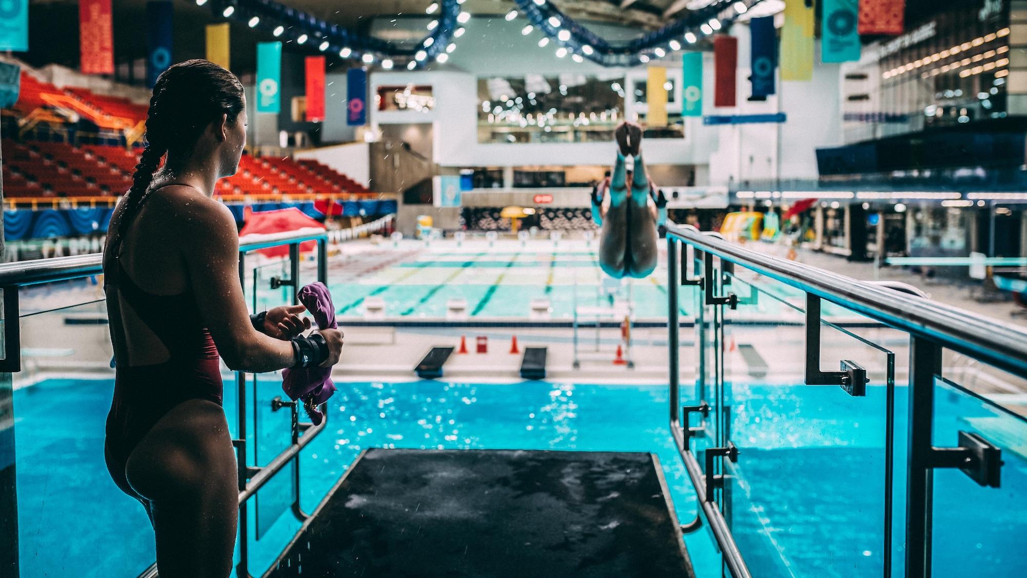 Caeli McKay (gauche) regarde sa partenaire Meaghan Benfeito plonger à l'entraînement.