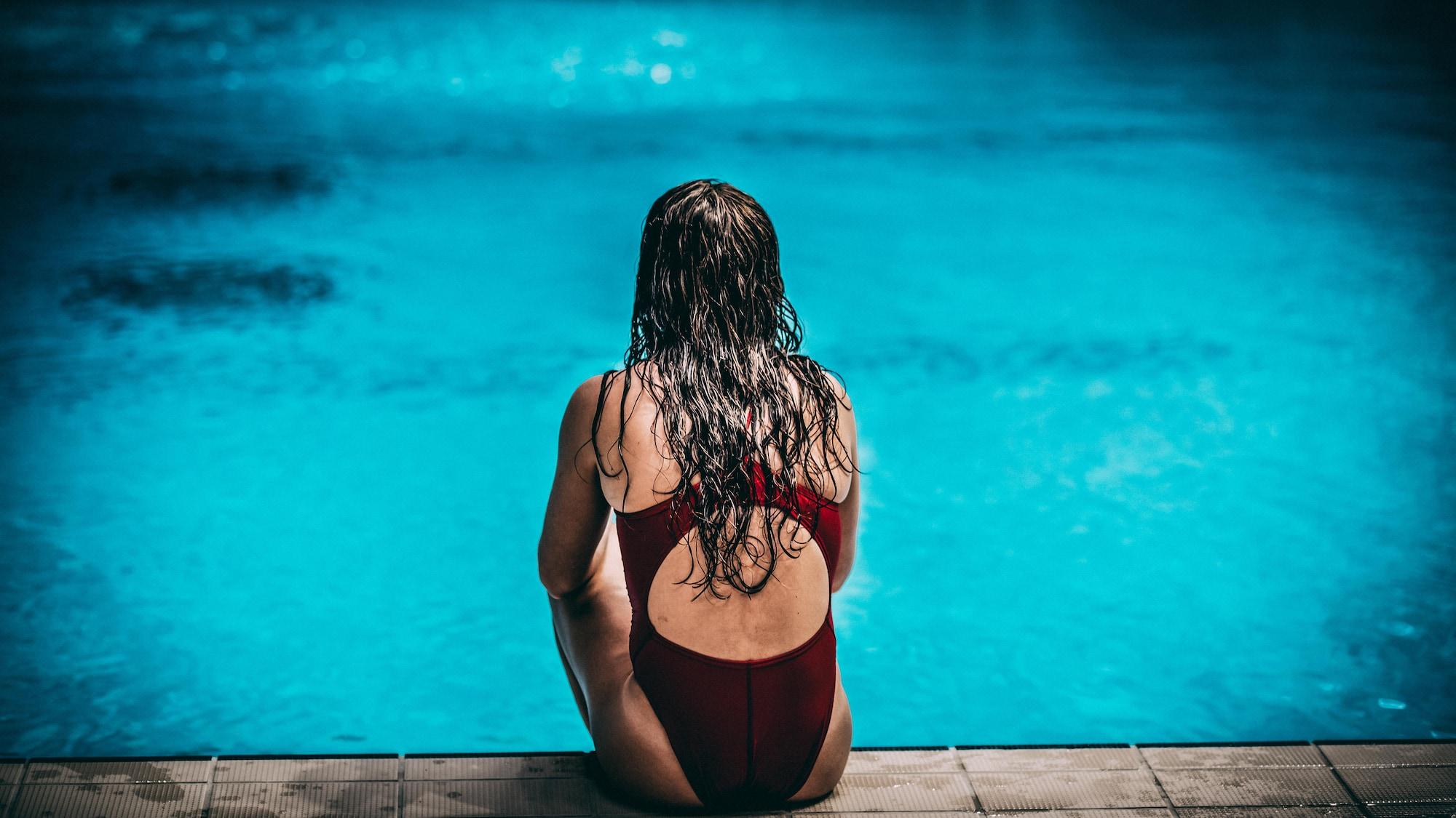 Caeli McKay est assise sur le bord du bassin de plongeon.