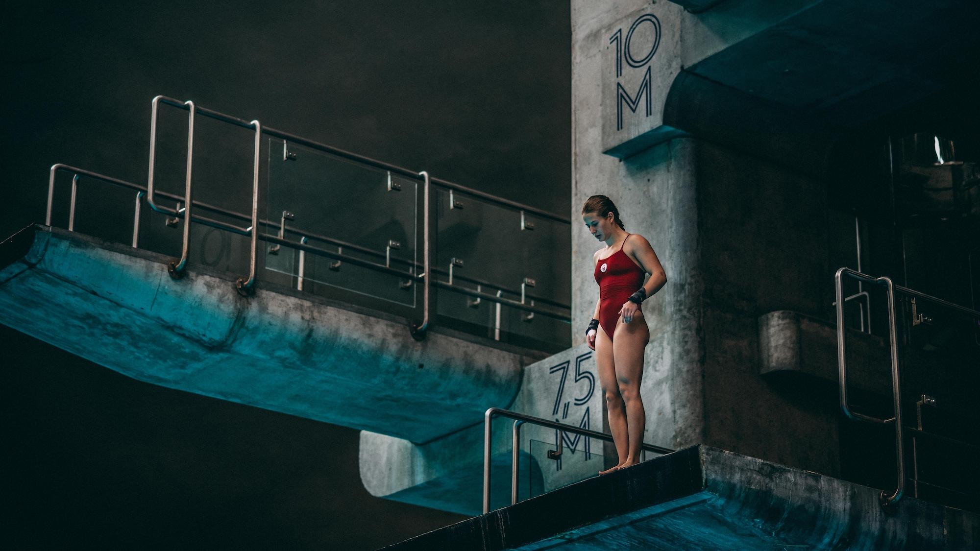 Postée sur la tour de 10 mètres, la plongeuse Caeli McKay regarde en bas en direction du bassin.
