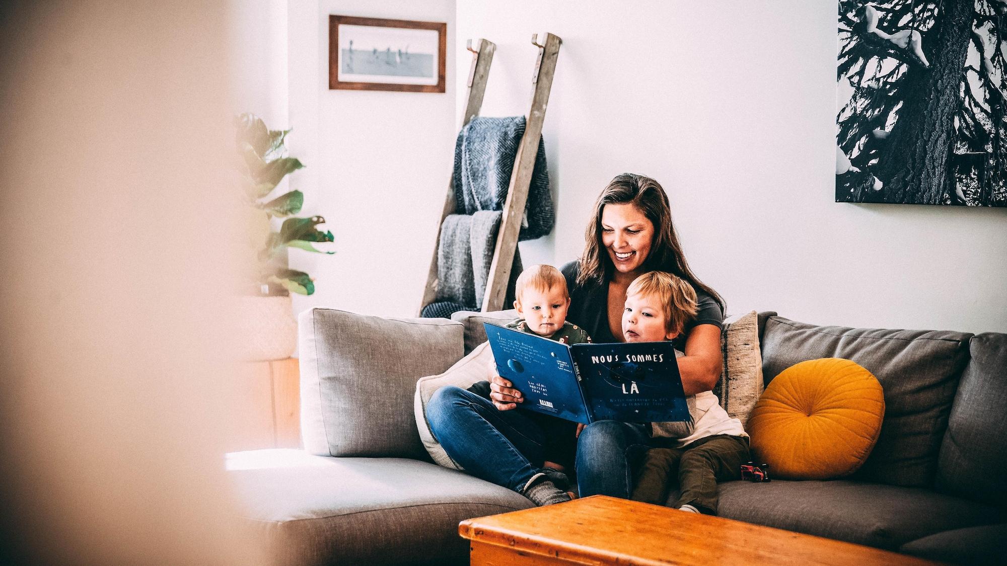 Elle leur lit un livre.
