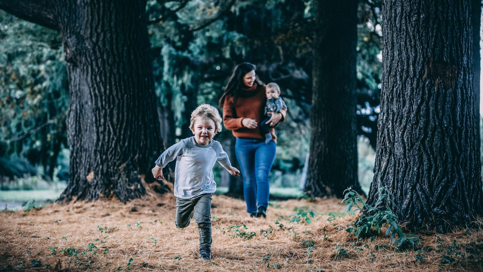 Elle marche dans la forêt en tenant son fils Cohan dans ses bras, tandis que son autre fils Quinn court en avant-plan.