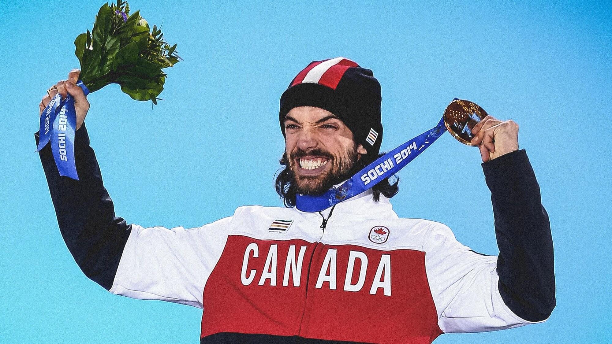 Charles Hamelin sourit à pleines dents en soulevant sa médaille.