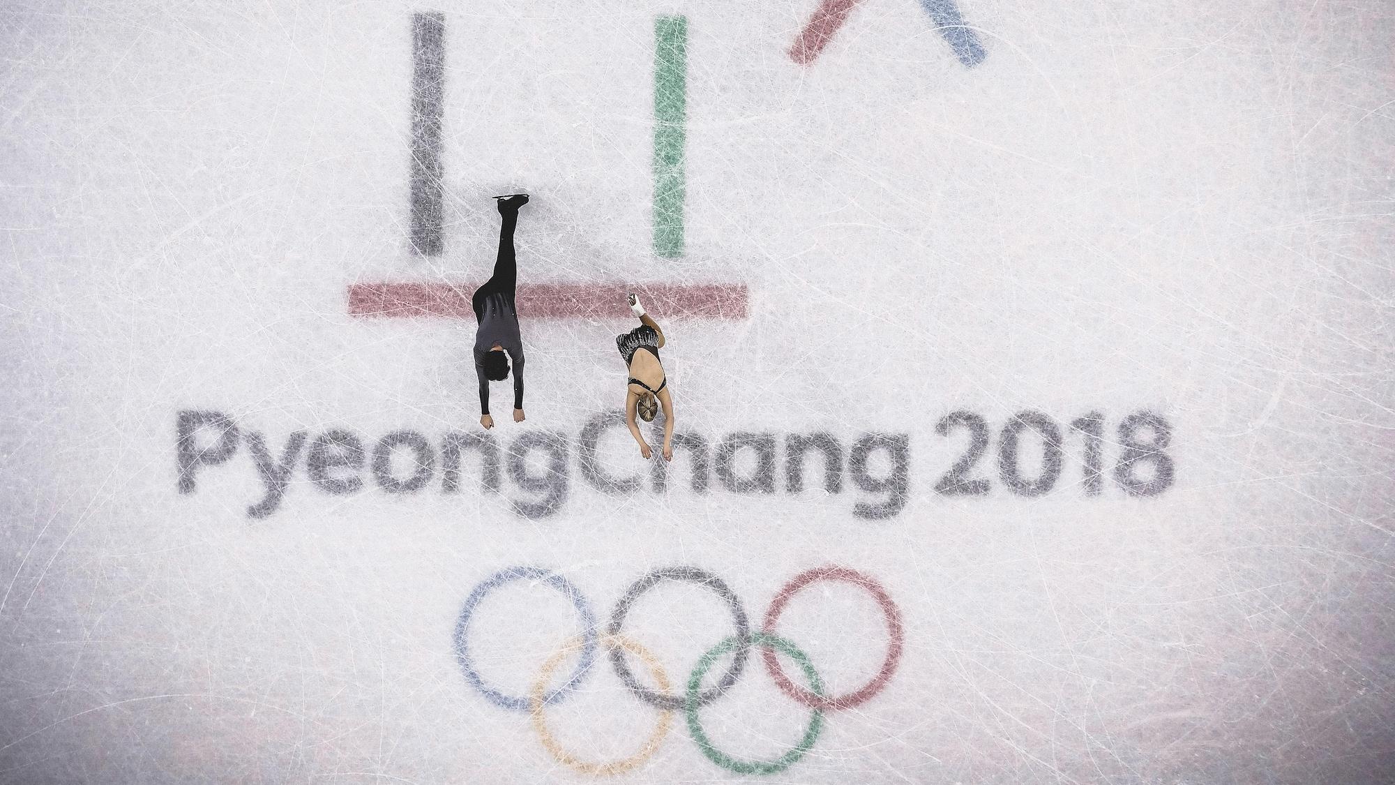 Charlie Bilodeau et Julianne Ségiun patinent sur le logo des Jeux olympiques de Pyeongchang, au centre de la patinoire.