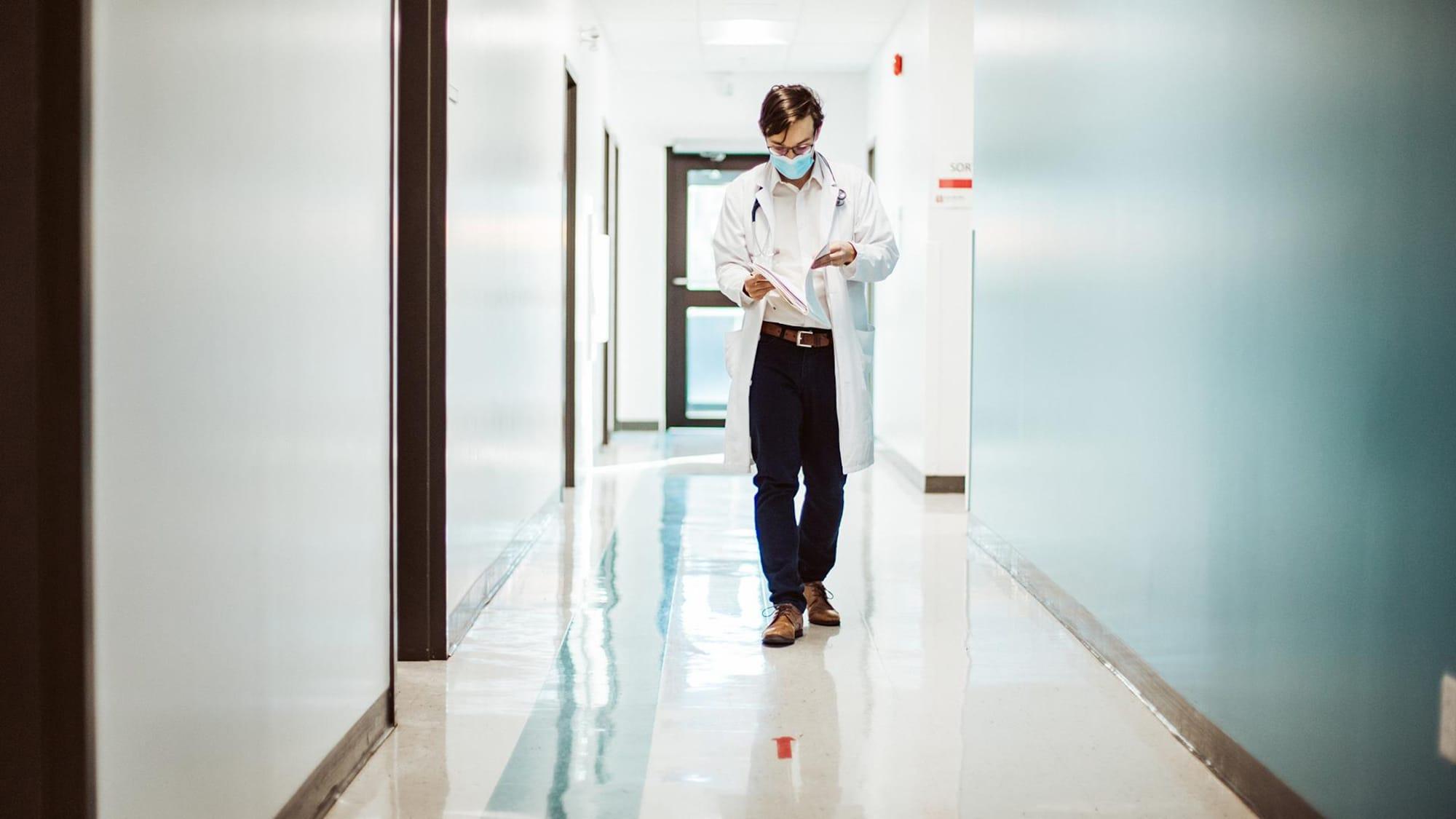 Le Dr Simard marche en lisant un dossier.
