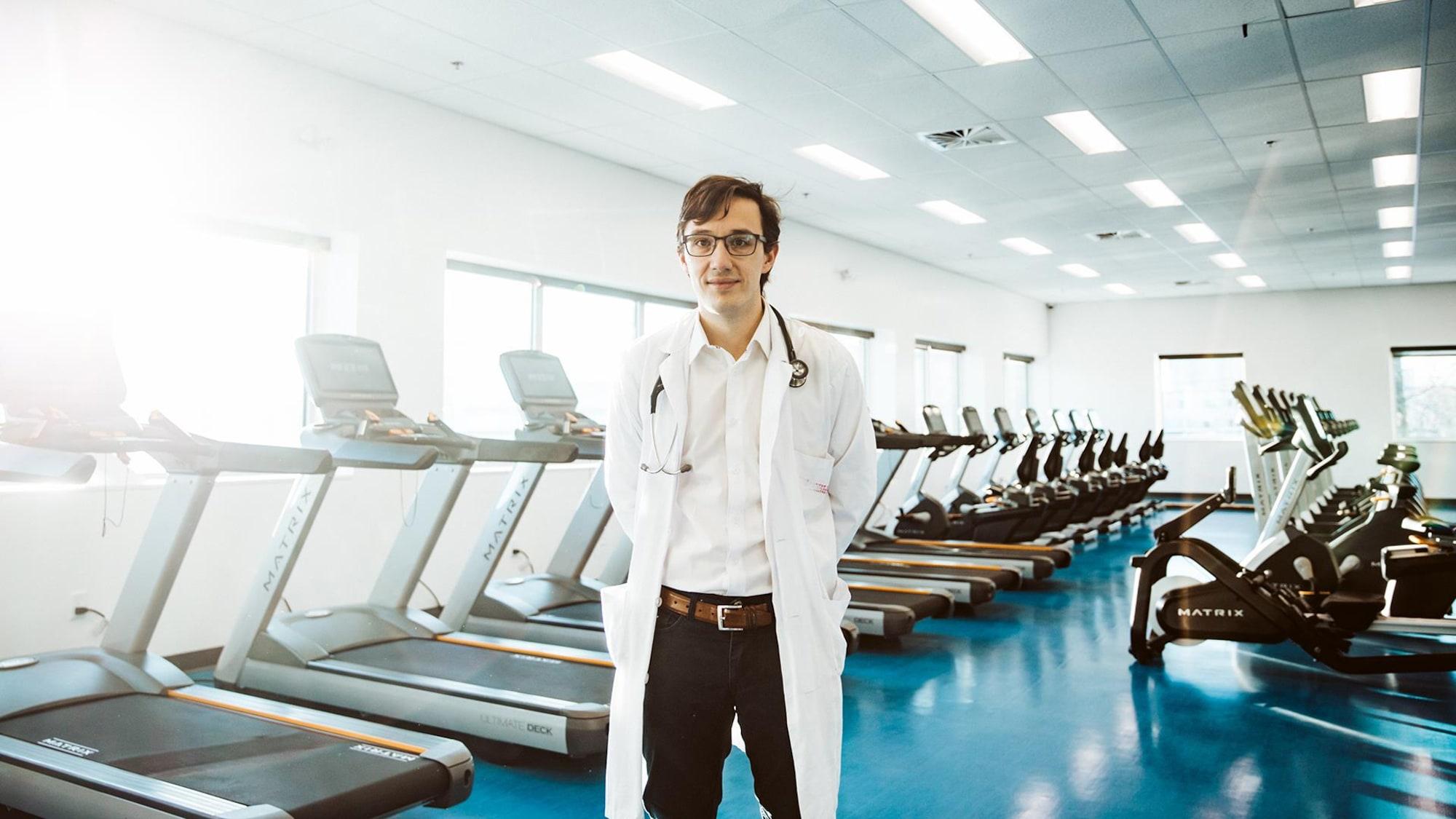 Le médecin se tient debout devant une série de tapis roulants.