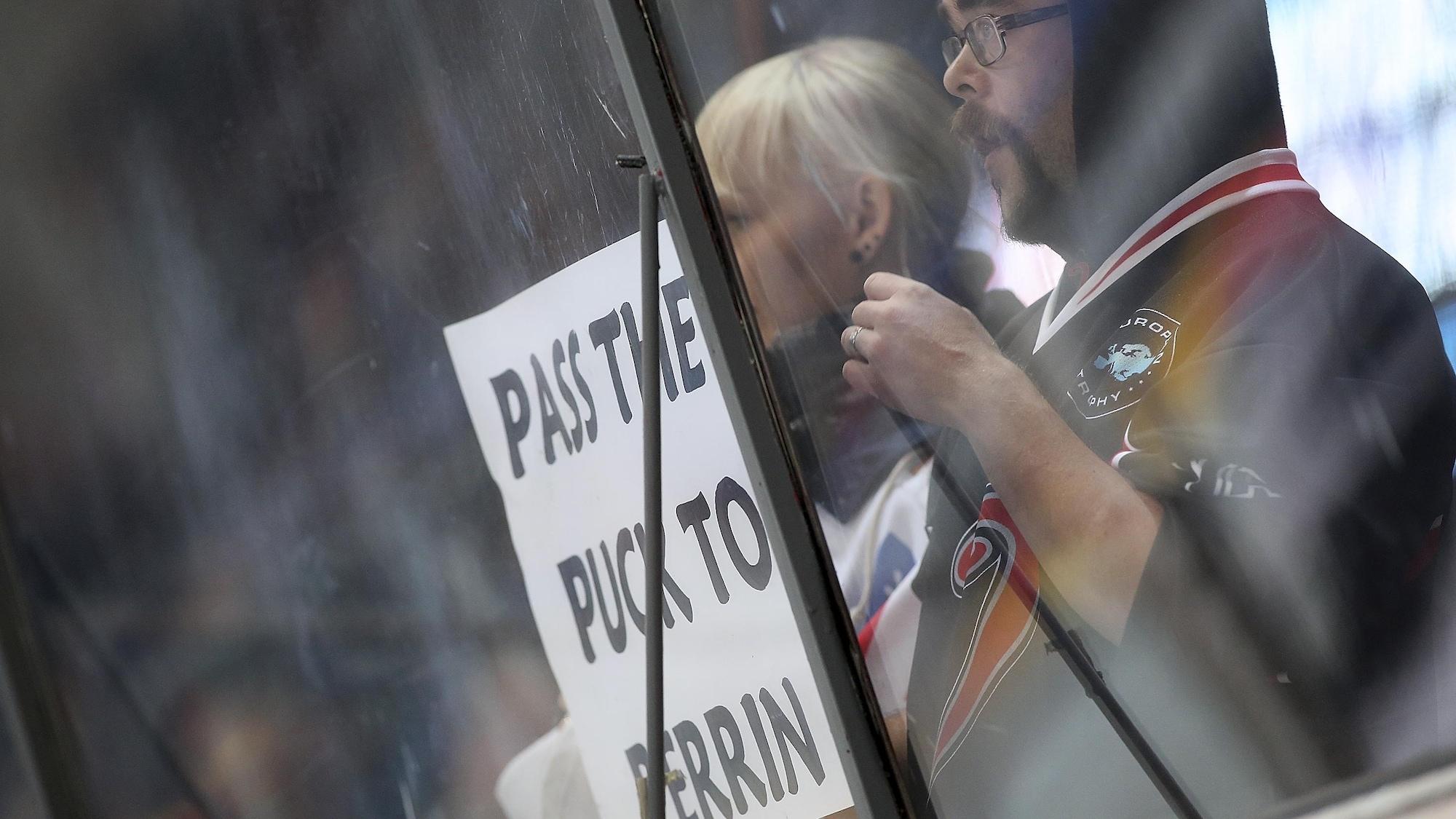 Deux partisans tiennent une affiche sur laquelle est écrit « Passez la rondelle à Perin ».
