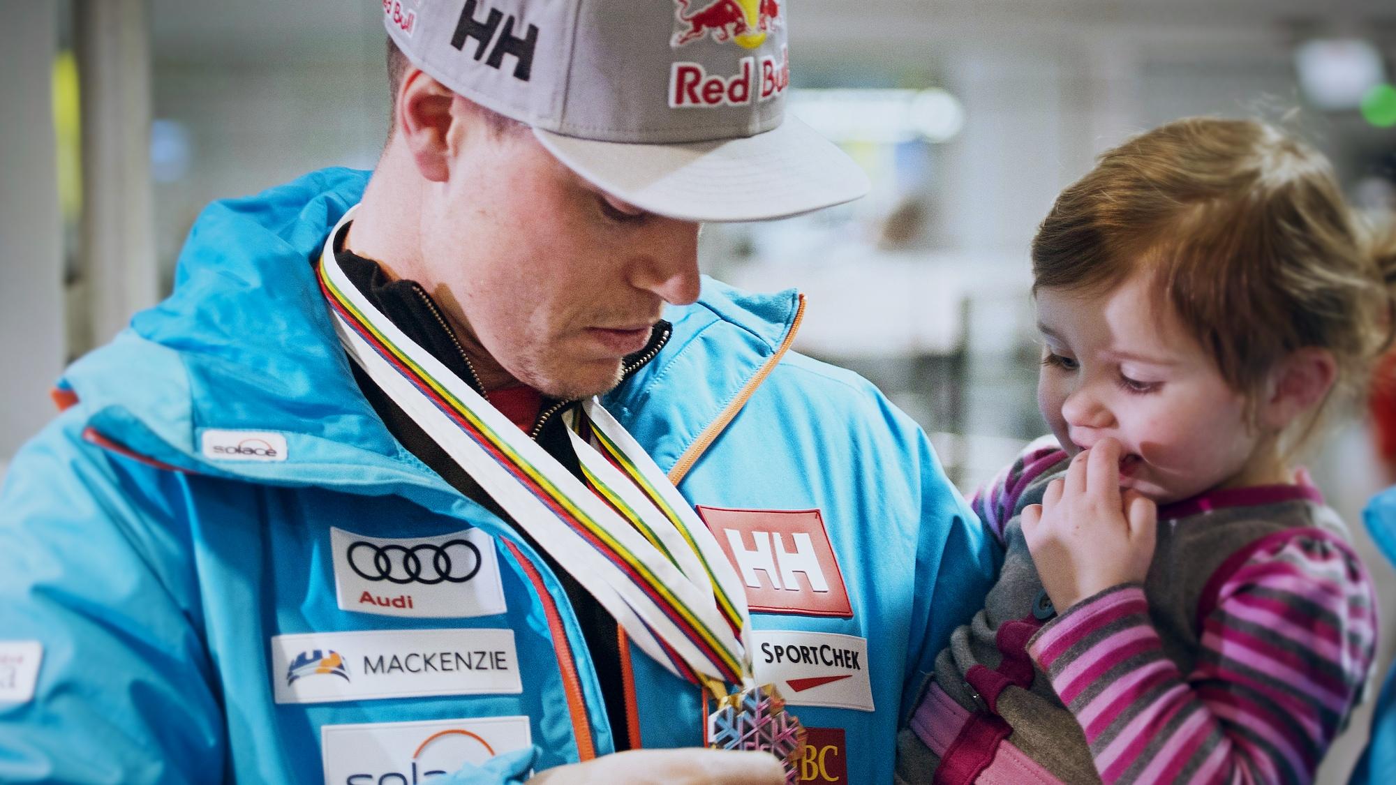 Erik Guay montre ses médailles à sa fille Marlo à son retour des mondiaux de ski alpin, en février 2017.