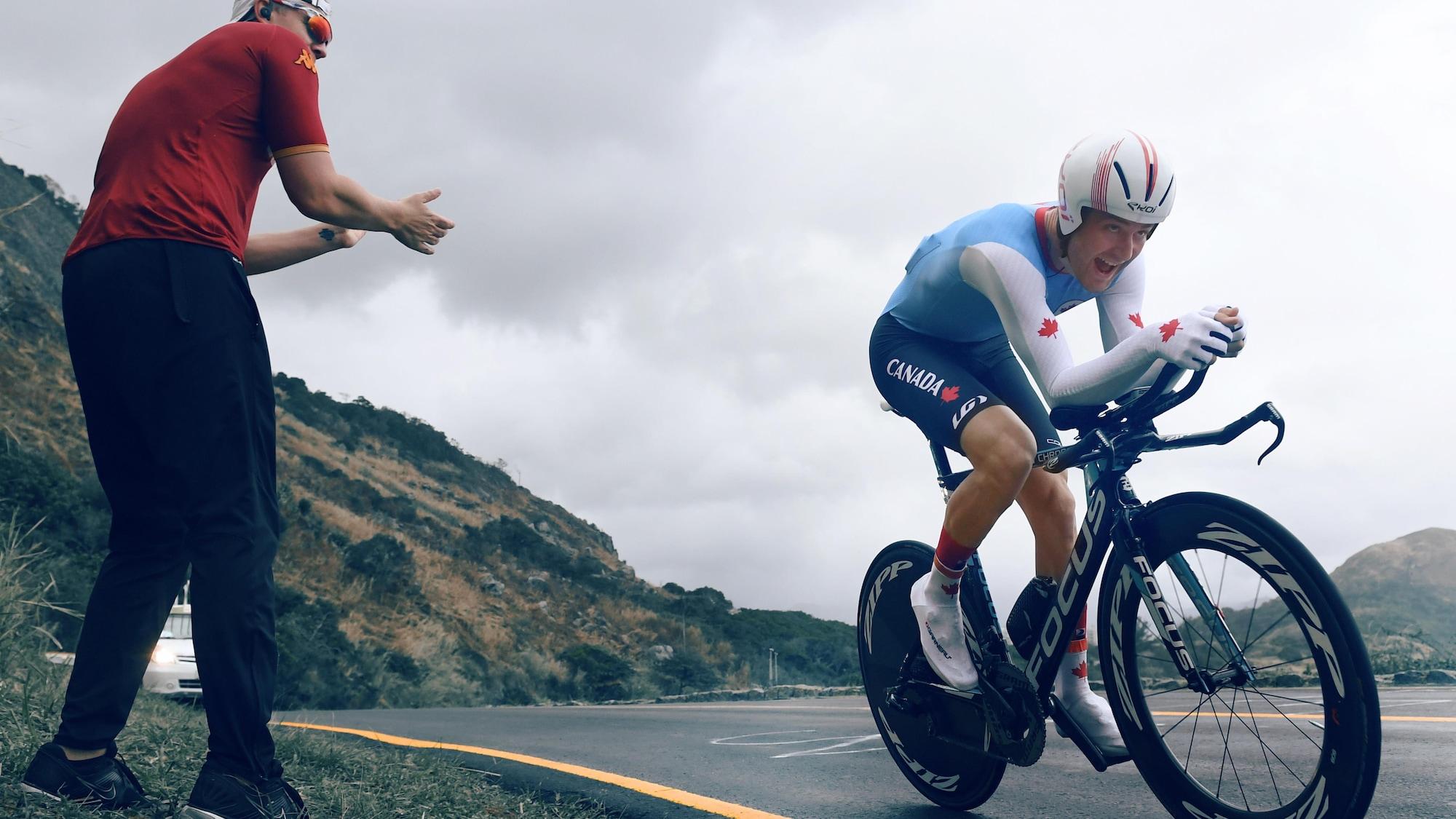 Un spectateur encourage le cycliste canadien Hugo Houle, qui passe tout près de lui.