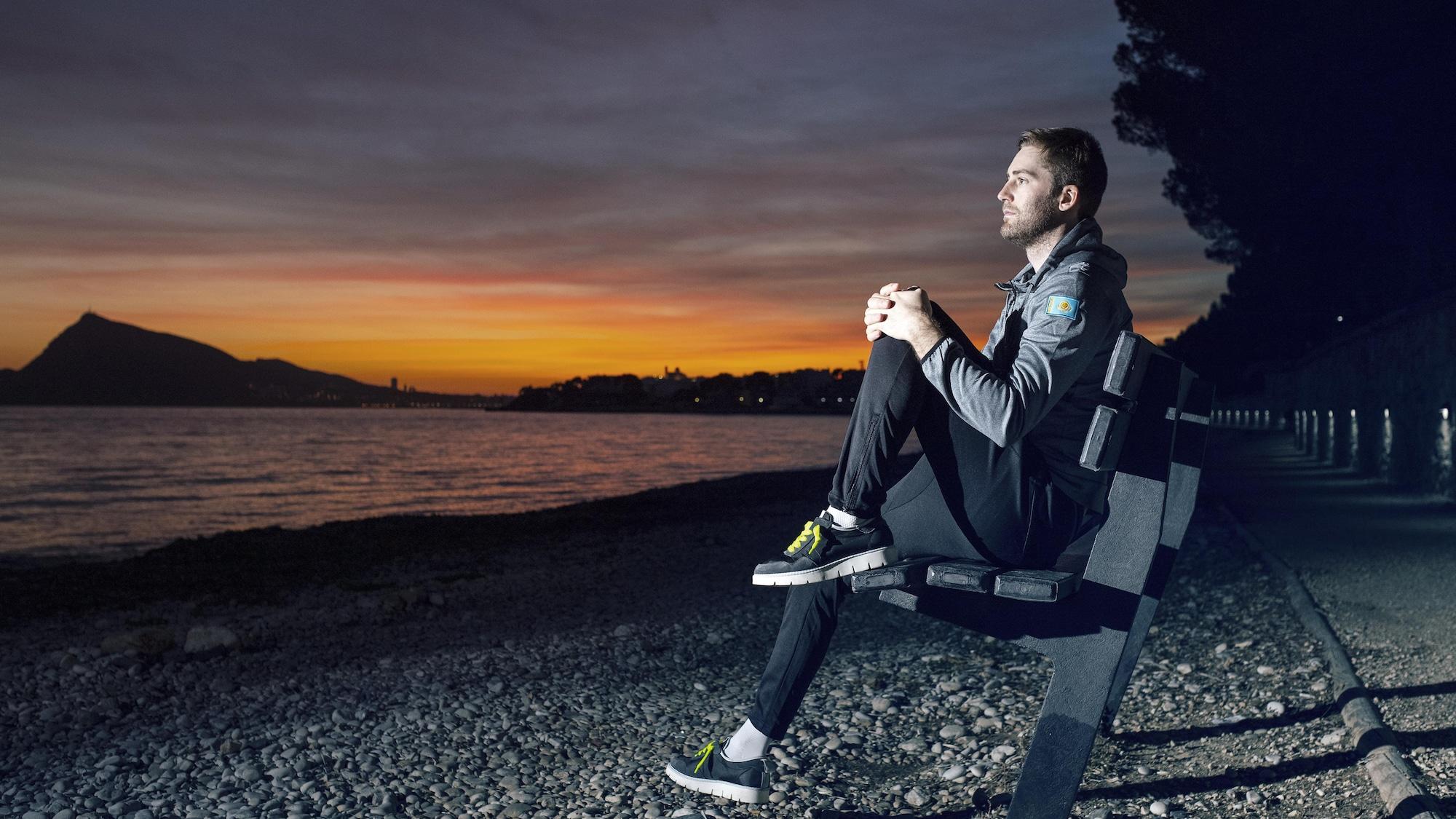 Hugo Houle est assis sur un banc devant un lac.