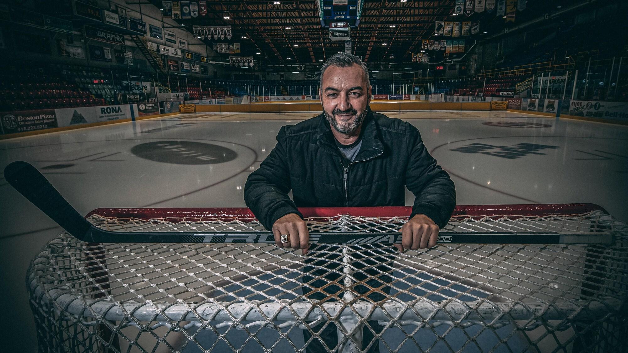 L'ex-joueur de hockey est appuyé sur un but et regarde la caméra en souriant.