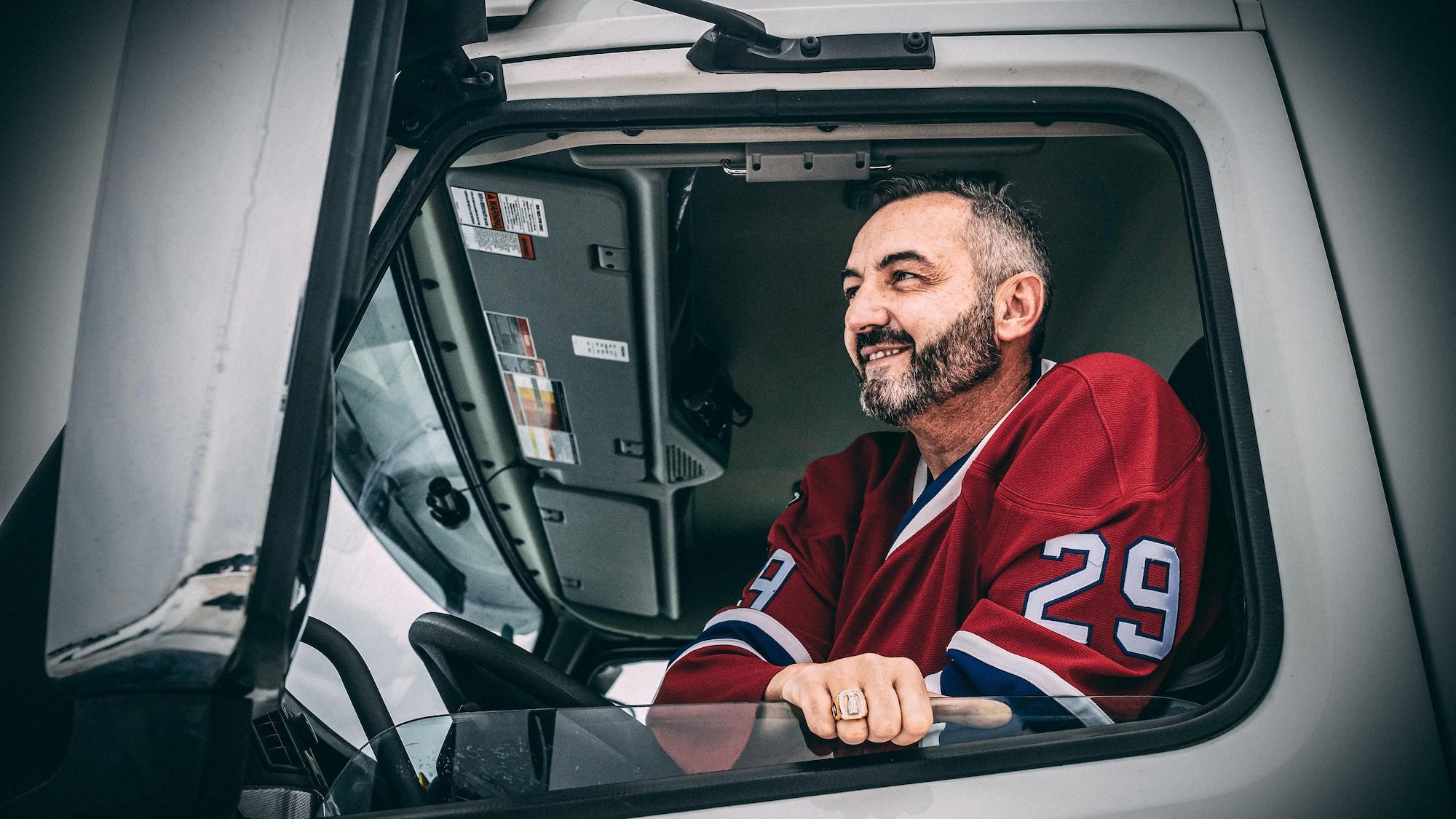 L'ex-hockeyeur est assis dans la cabine de son camion.