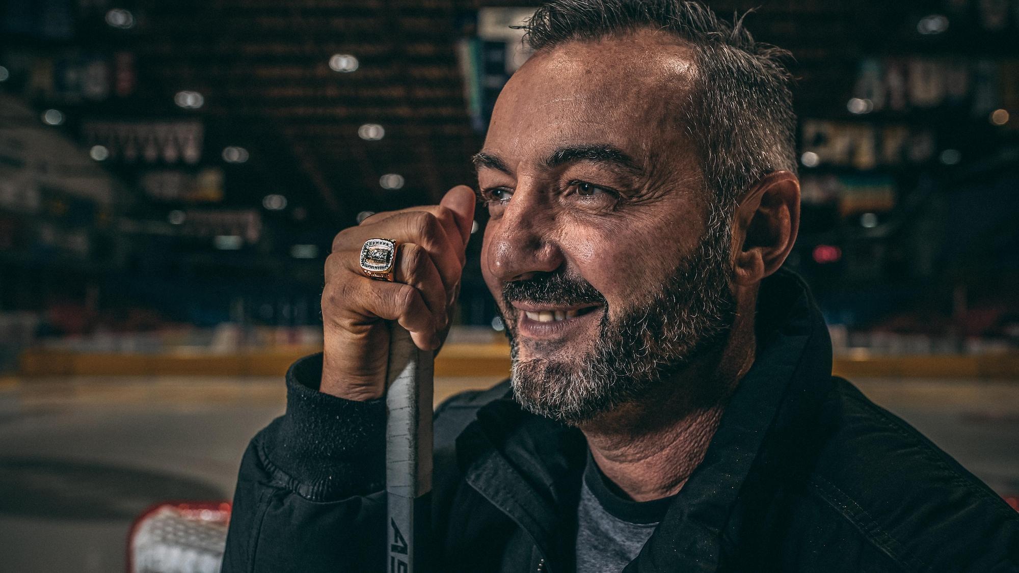 L'ex-hockeyeur sourit.