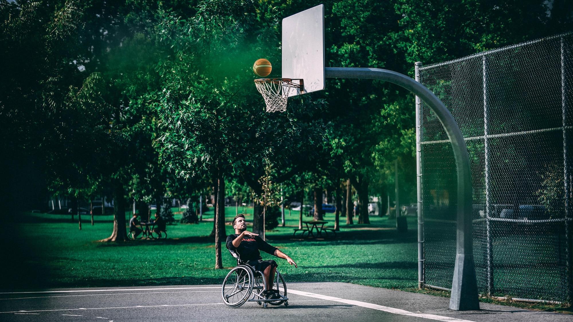 Jonathan Vermette lance le ballon vers le panier, dans un parc de Montréal.