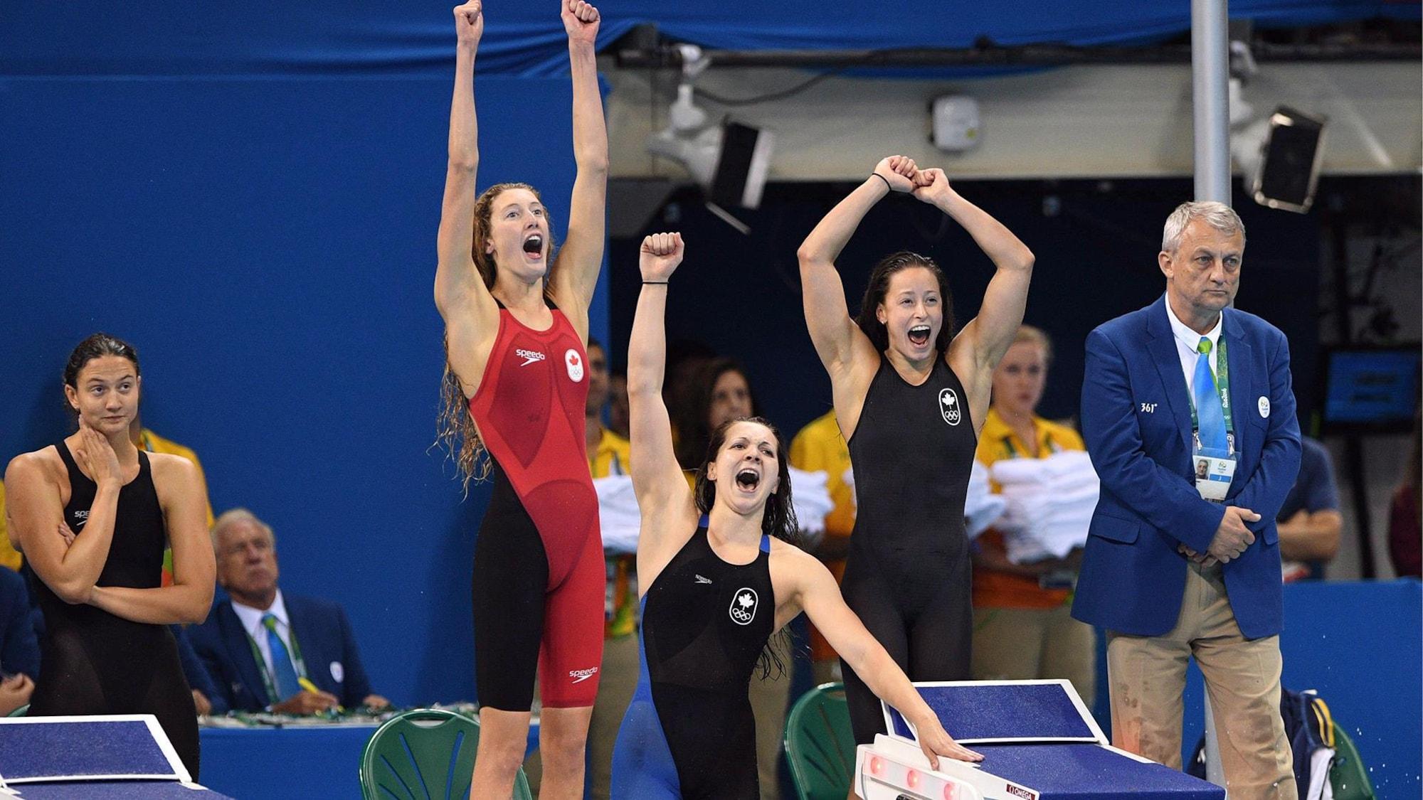 Trois nageuses lèvent les bras et crient de joie.