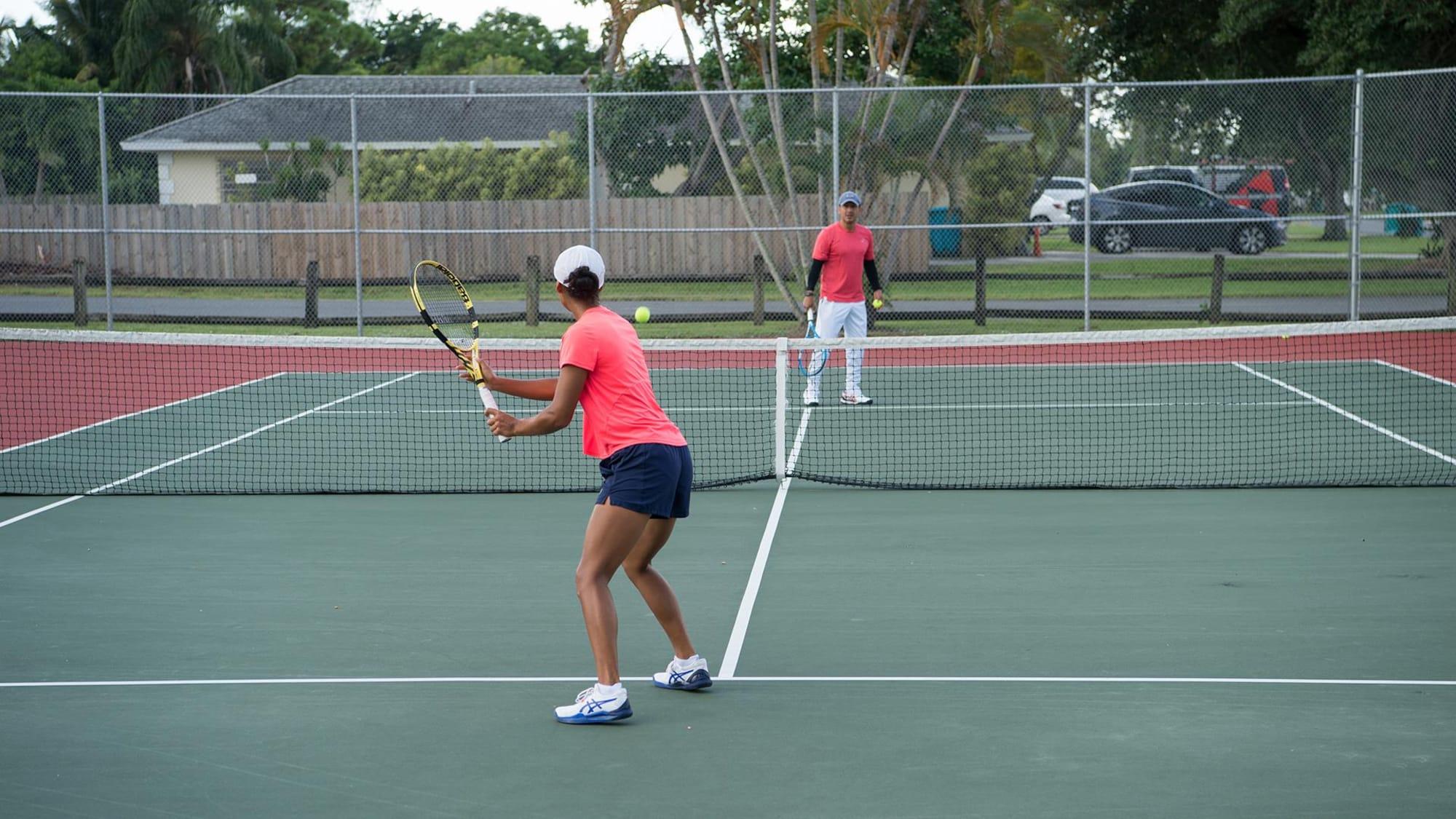 Une joueuse de tennis s'apprête à frapper une balle sous le regard d'un homme.