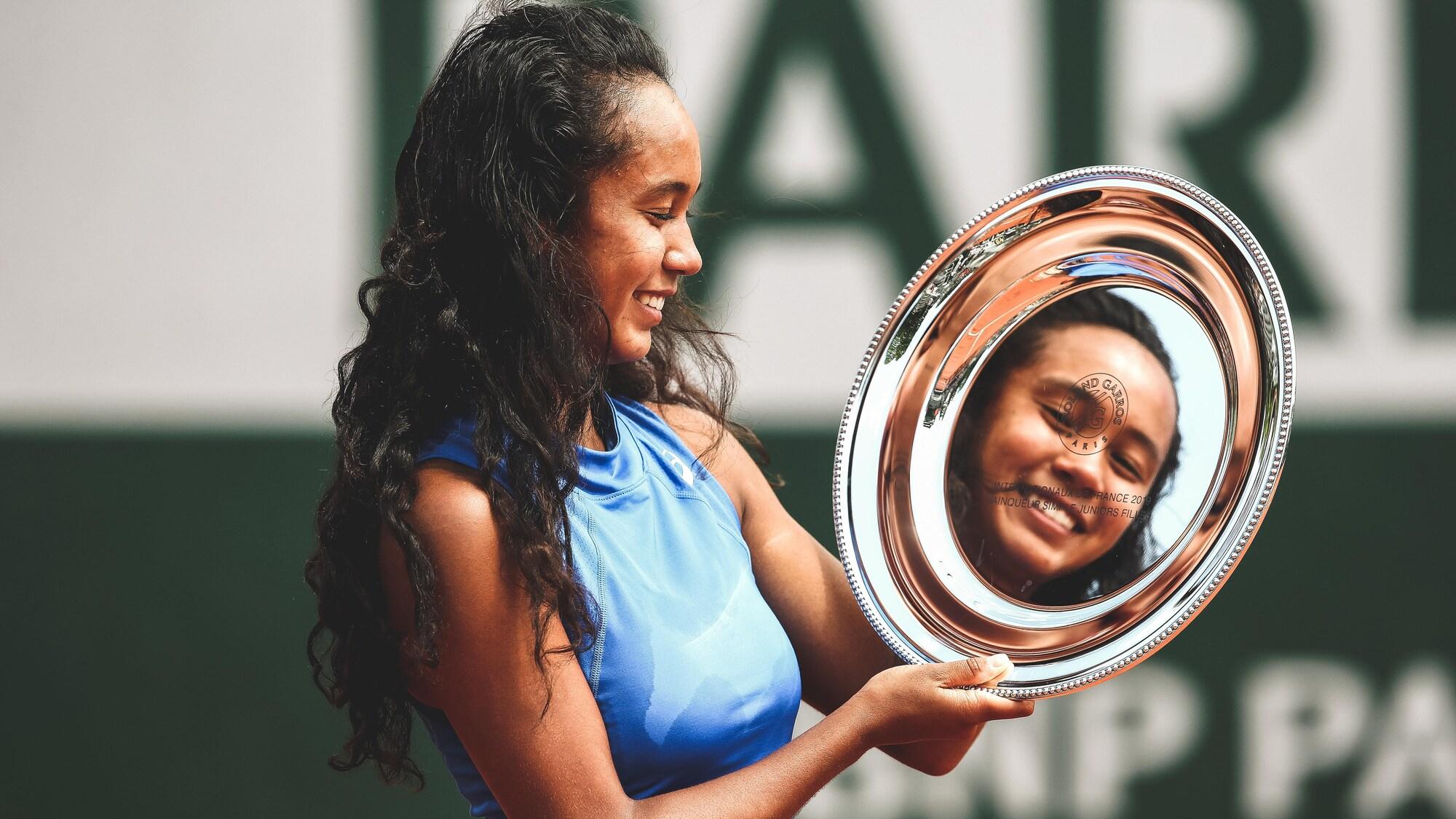 Leylah Annie Fernandez regarde en souriant le reflet de son visage que lui renvoie le trophée.