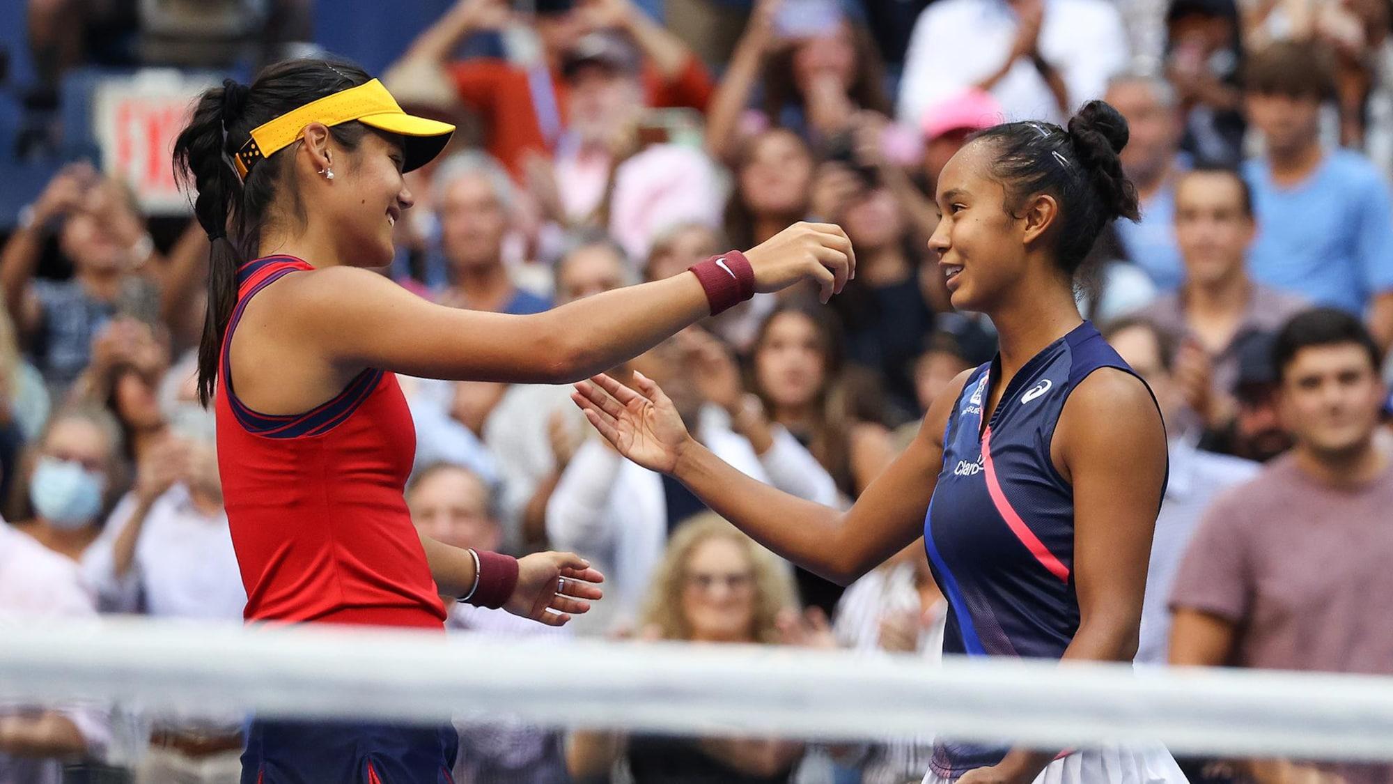Deux femmes se  font l'accolade sur un terrain de tennis.