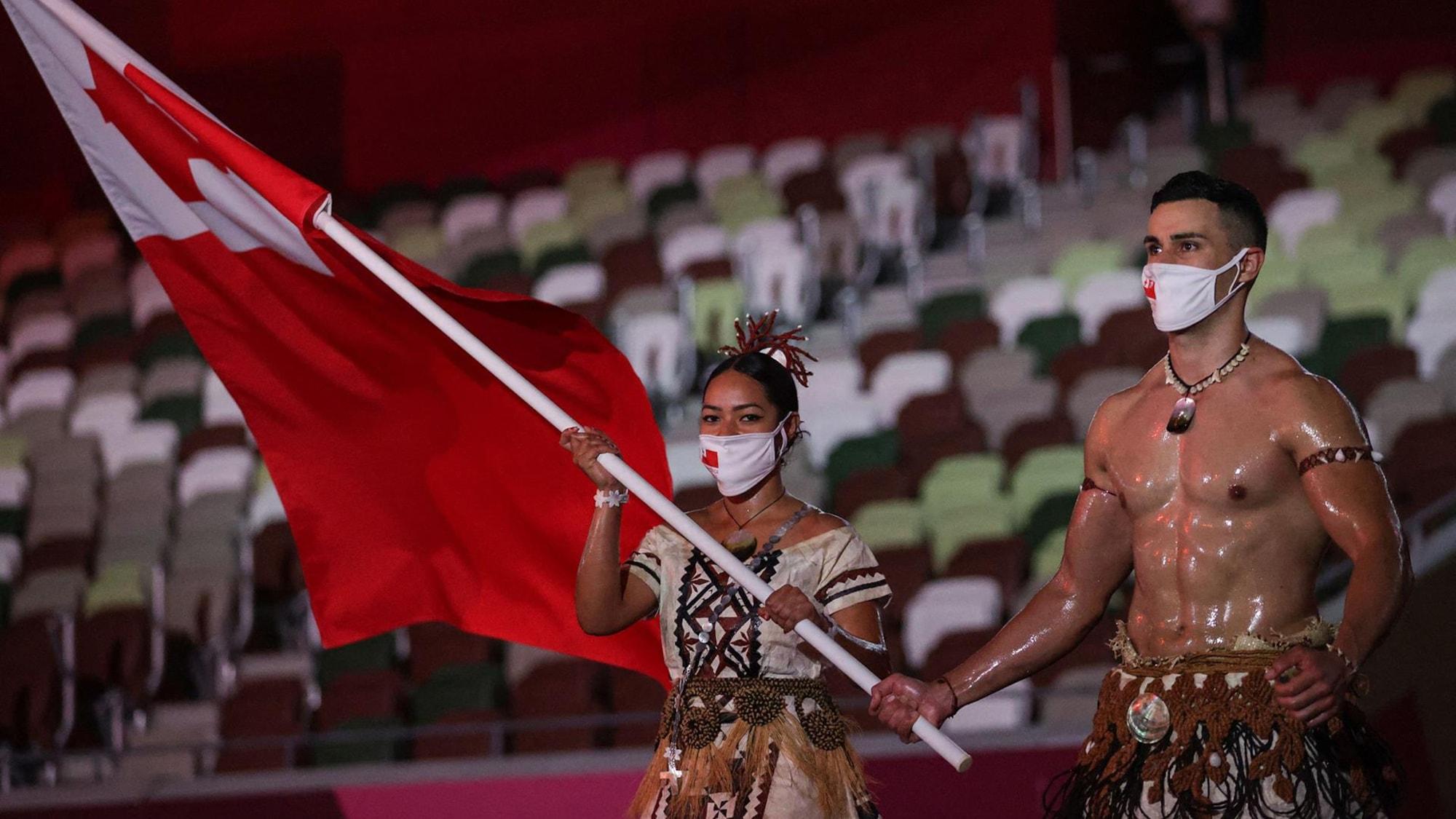 Une femme et un homme tiennent un drapeau et marchent.