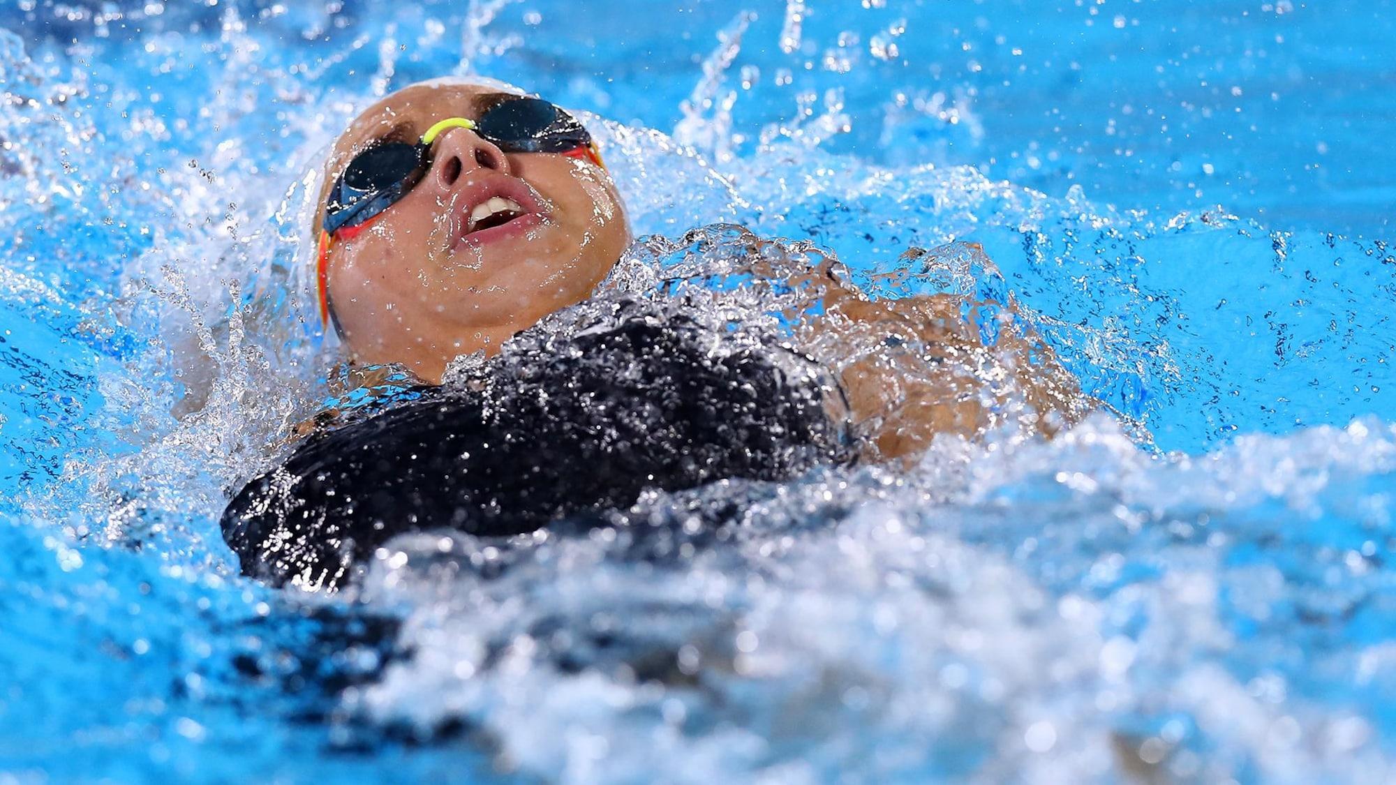 Une athlète nage sur le dos.