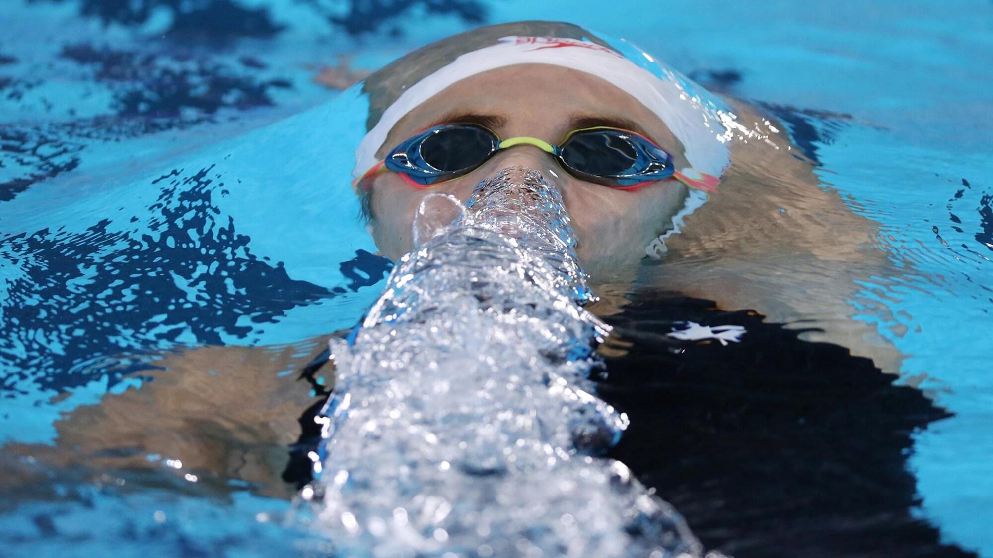 Une nageuse fait des bulles en expirant sous l'eau.