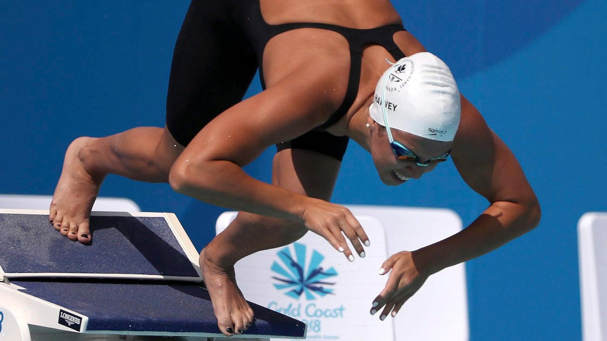 La nageuse, sur le plot de départ, s'apprête à s'élancer dans l'eau.