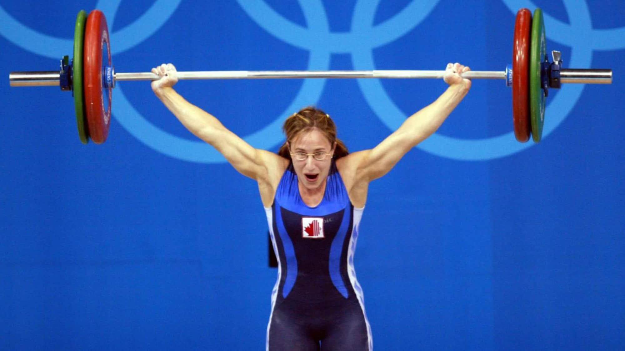 Maryse Turcotte sourit en levant une barre au-dessus de sa tête pendant la compétition d'haltérophilie des Jeux d'Athènes.