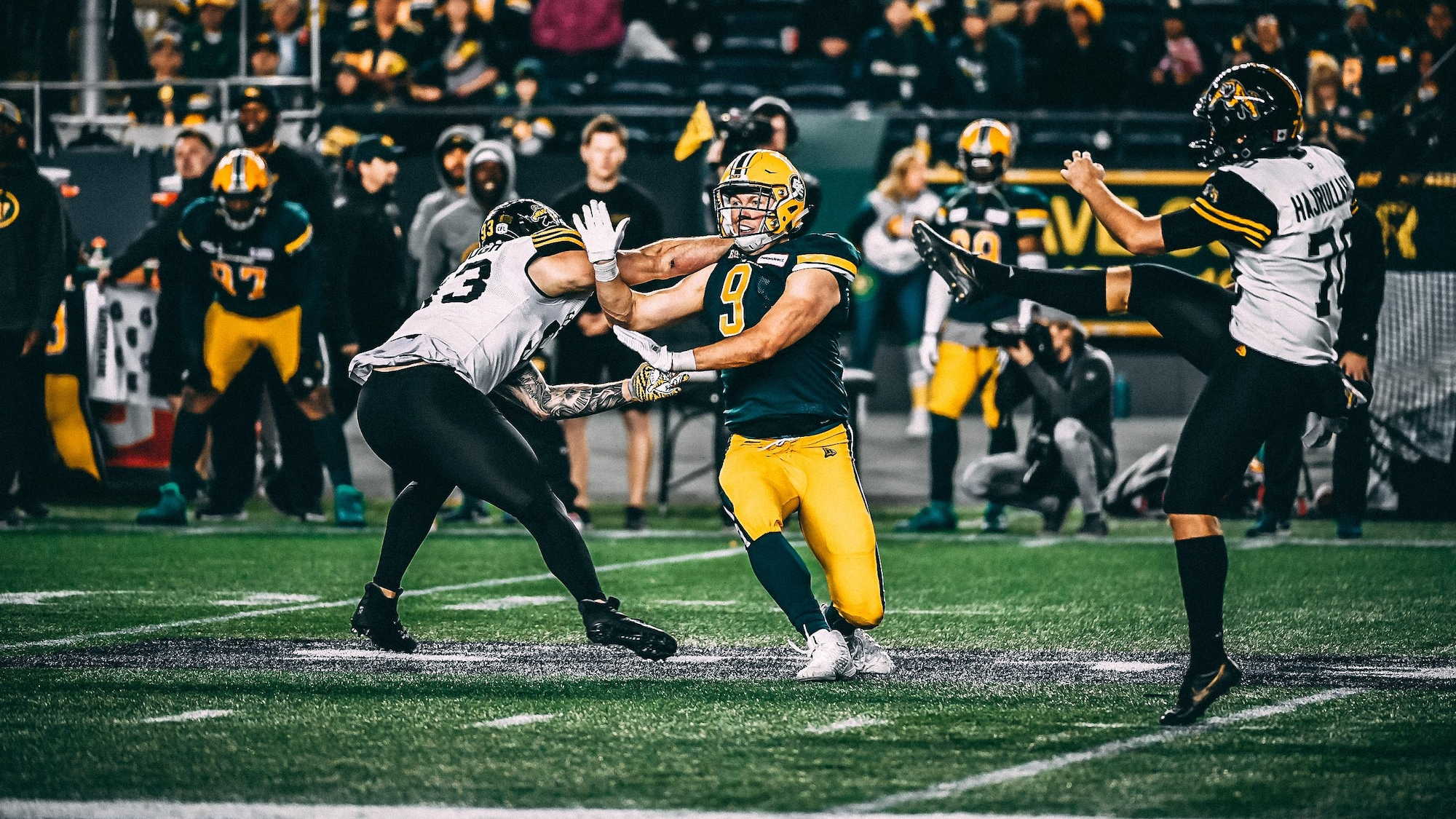 Mathieu Betts court vers le botteur de dégagement des Tiger-Cats de Hamilton pendant un match.