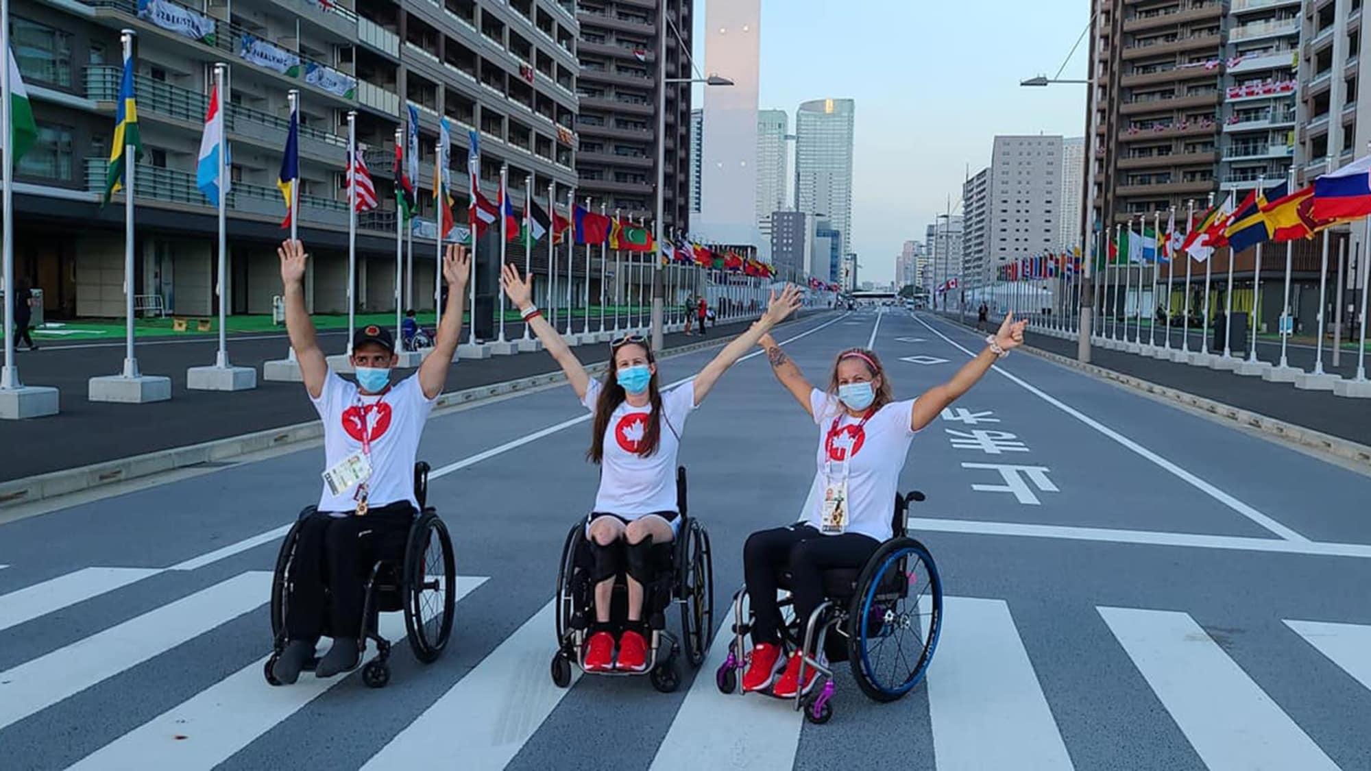 Il prend la pose les bras en l'air avec deux autres athlètes.