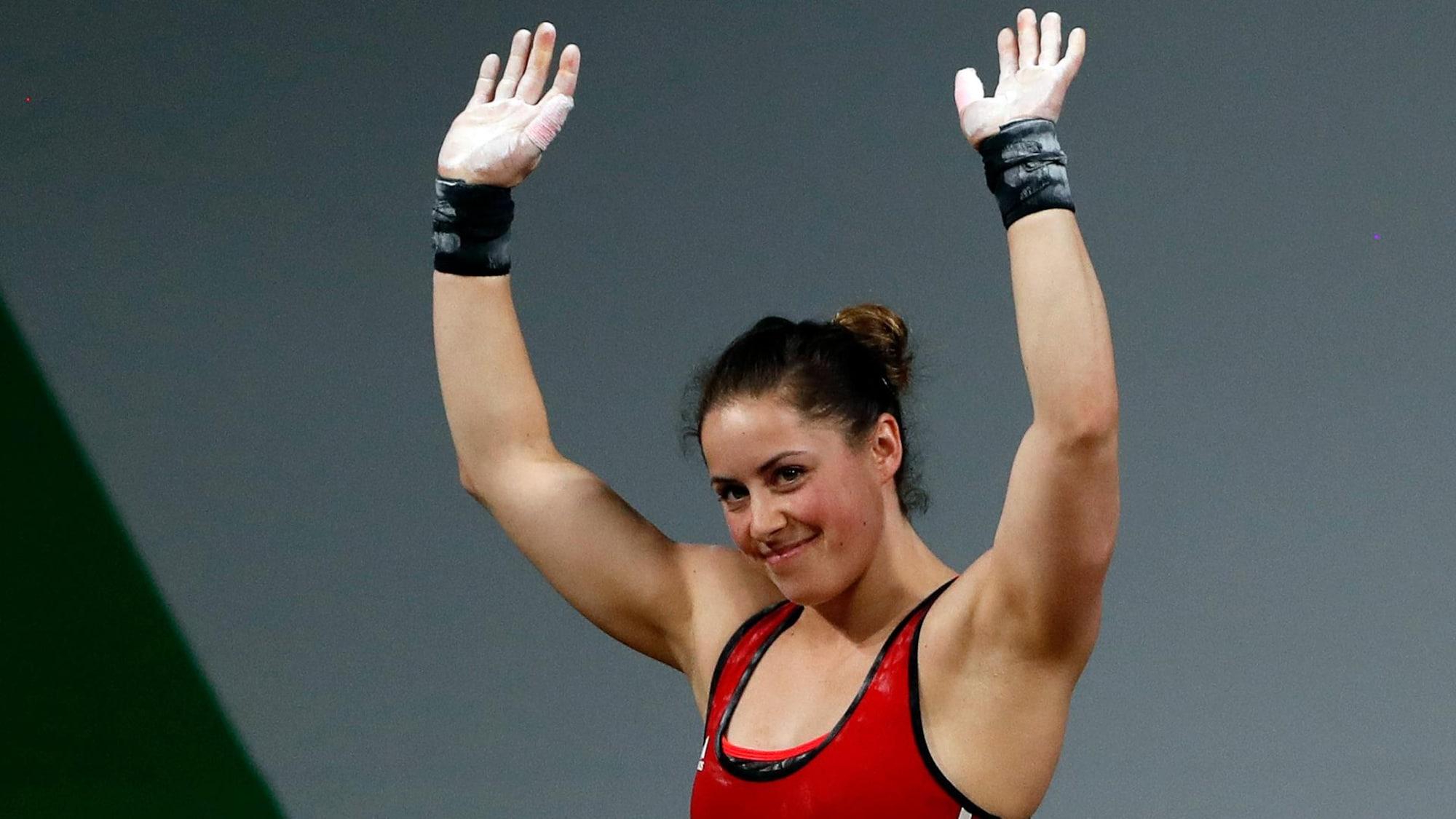 Une haltérophile lève les bras en souriant.