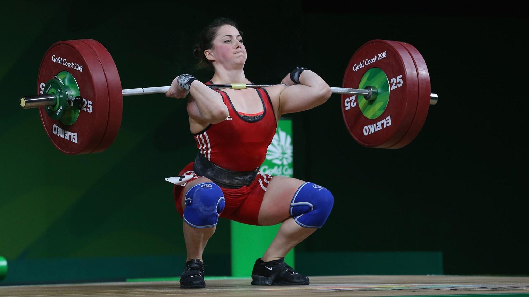 Une haltérophile soulève une barre pendant une compétition.