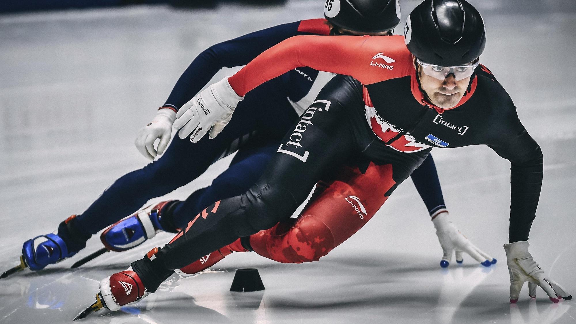 Un patineur de vitesse courte piste effectue un virage, suivi de prés par un adversaire.