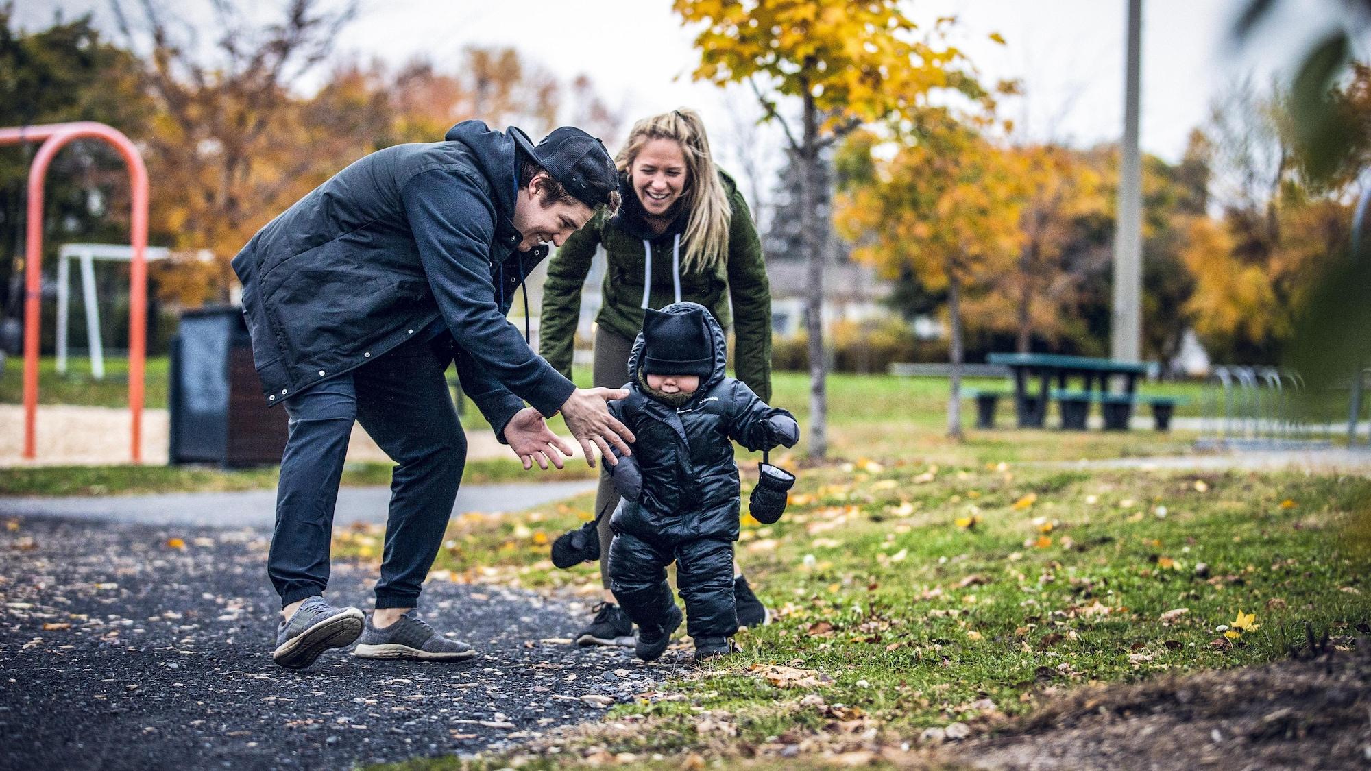 Mathéo marche dans un parc pendant que ses parents le regardent en riant.