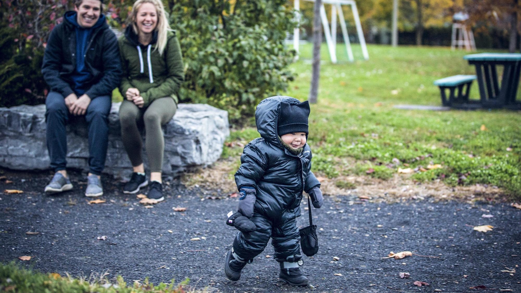 Maxime et Marylou, assis sur une roche dans un parc, regardent leur fils Mathéo marcher.