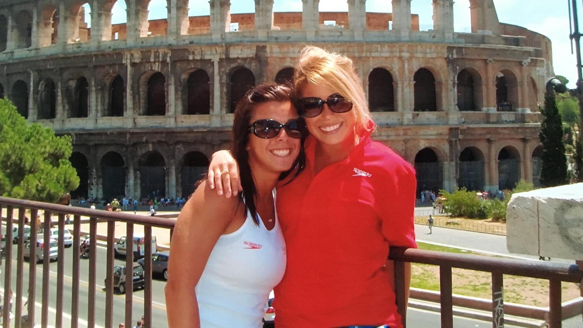 Deux jeunes femmes se tiennent par les épaules et sourient à la caméra.
