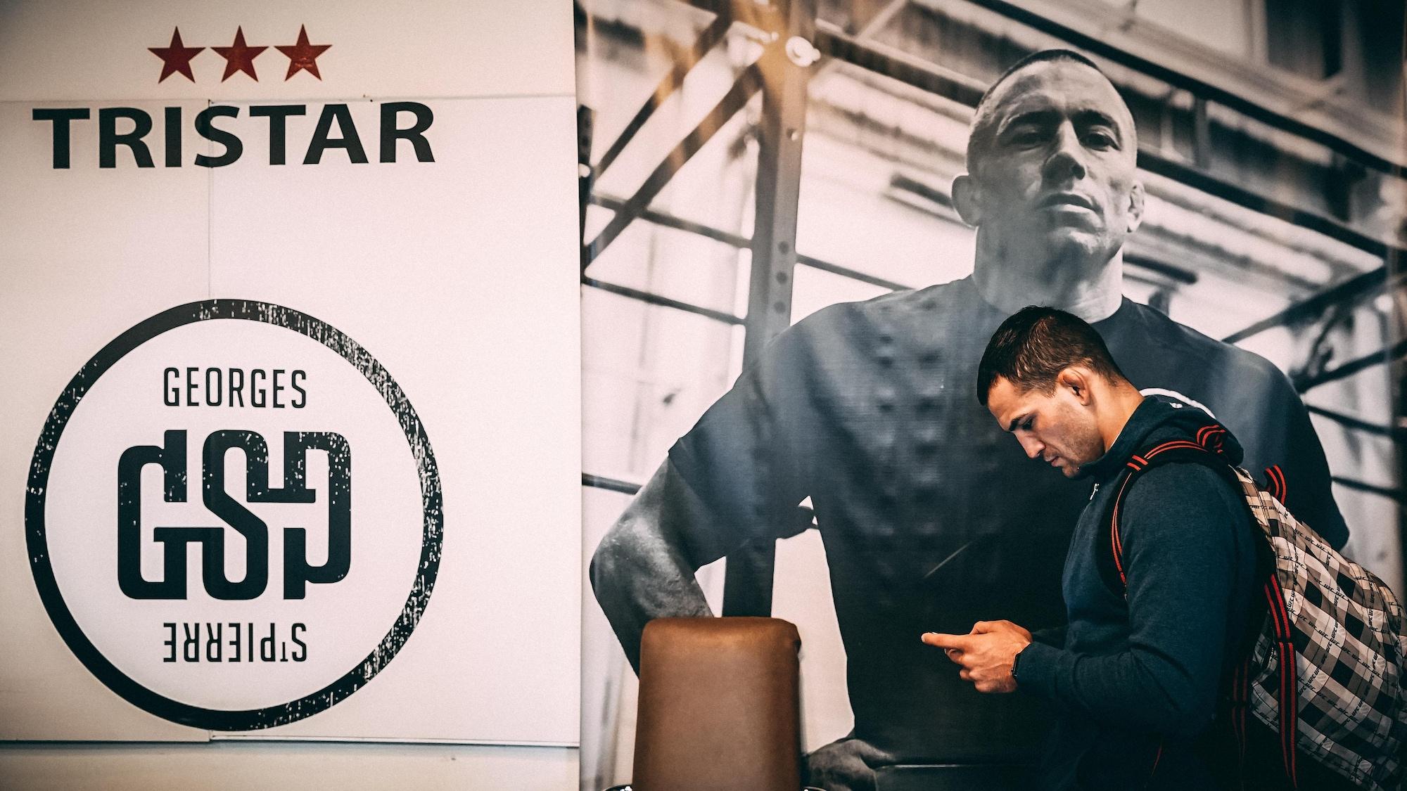 Mirsad Bektic consulte son téléphone en marchant devant une affiche montrant George St-Pierre.