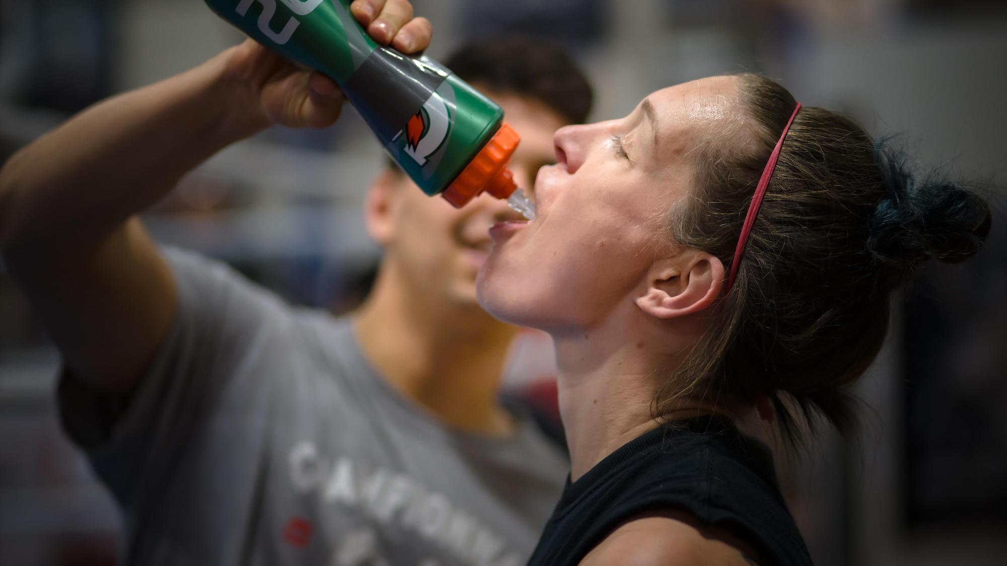 Une femme boit de l'eau venant d'une gourde tenue par une personne qui se tient à côté d'elle.