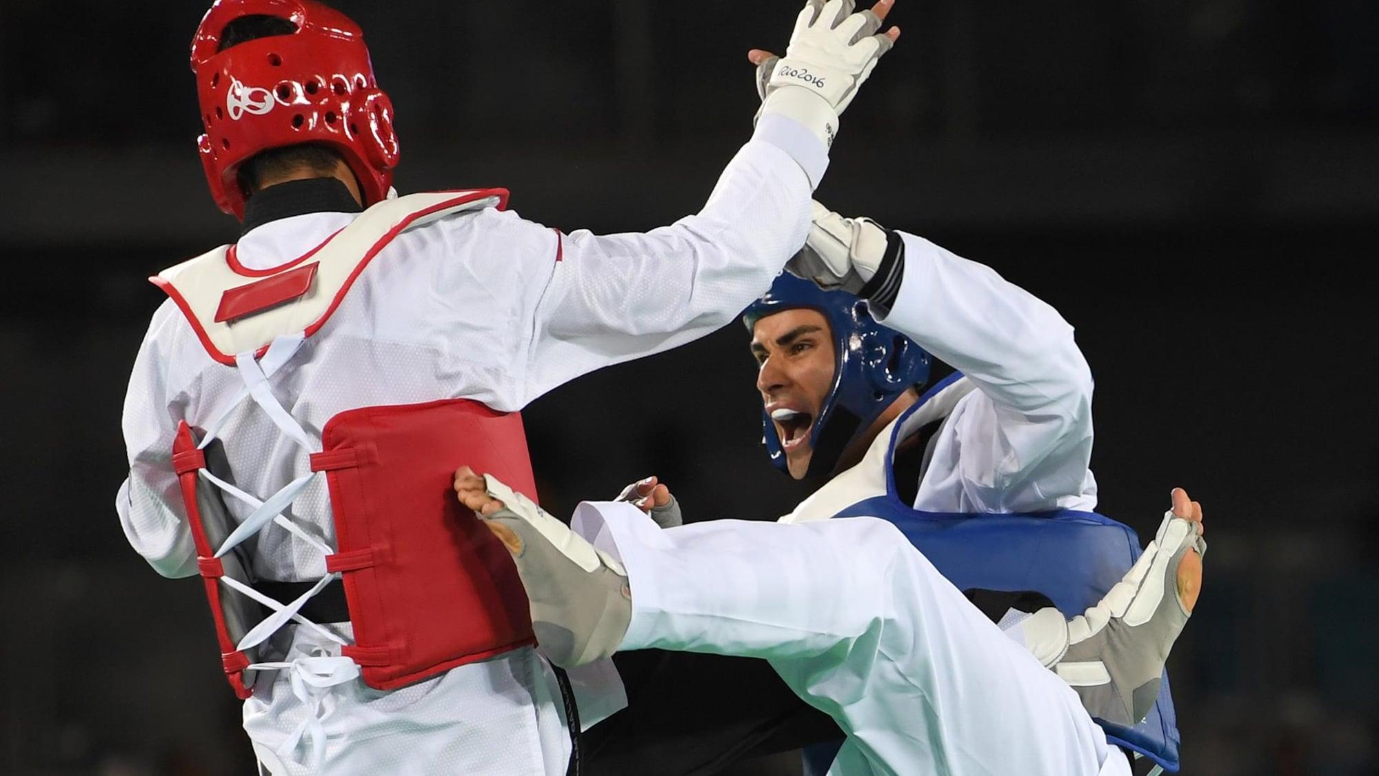 Deux athlètes de taekwondo se battent.