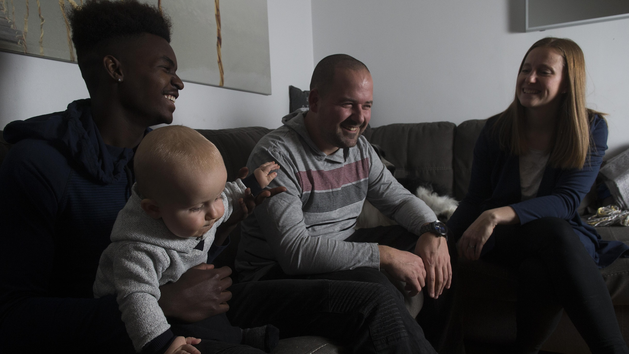 Prinzy Dessources, qui tient dans ses bras le petit Madden, est assis sur un divan près de son père et de sa mère.