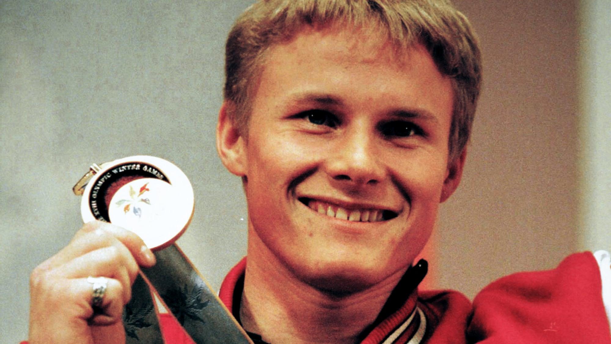 Ross Rebagliati tient sa médaille d'or en souriant.